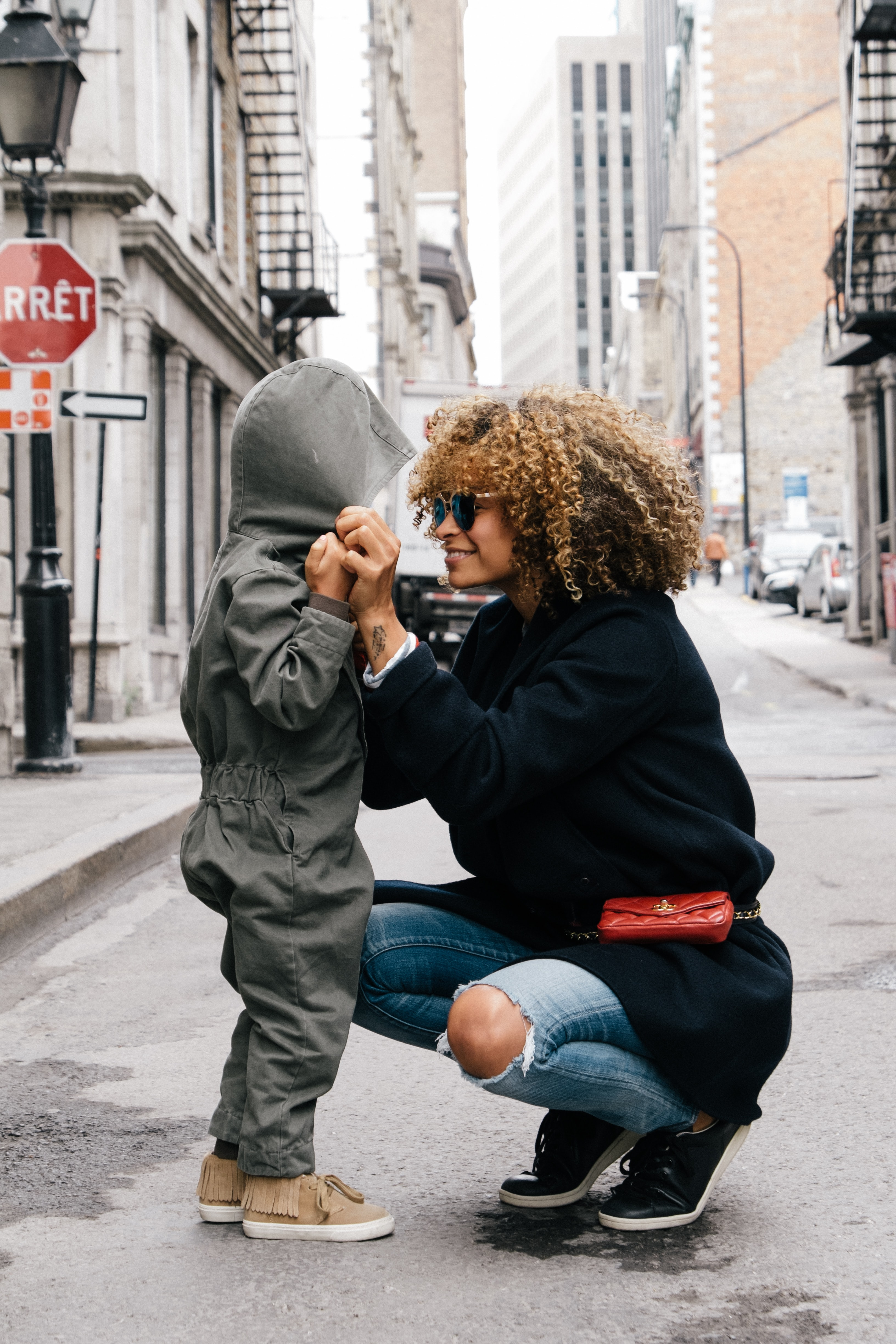 A mom with curly hair crouching in the street, Old Port of Montreal, smiling at her young child wearing an all in one outfit with the hood up