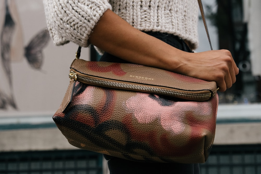 woman holding brown and pink floral leather crossbody bag