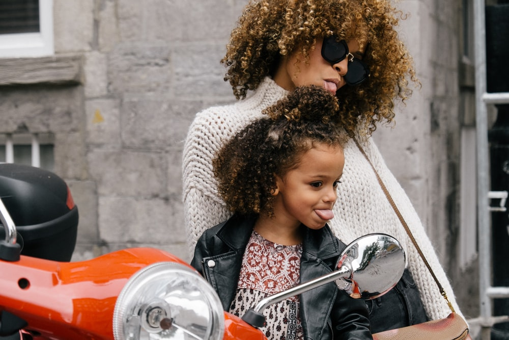 woman and girl showing their tongues beside motorcycle