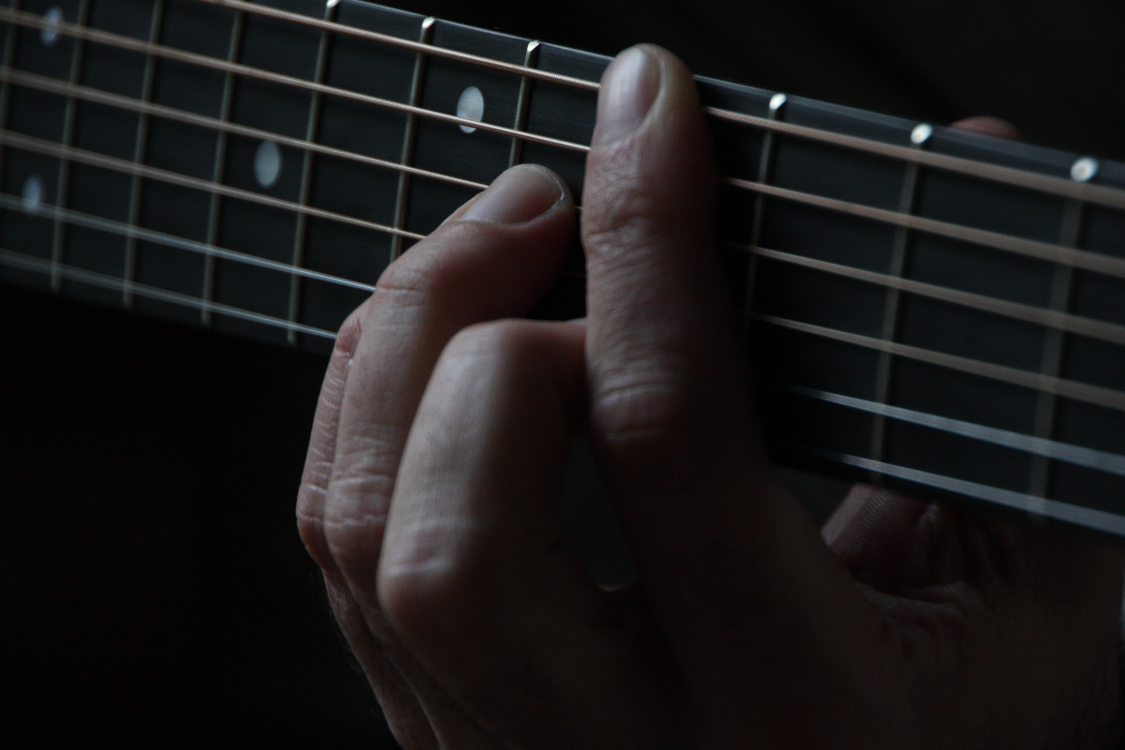 A close-up of a person's hands on the neck of a guitar