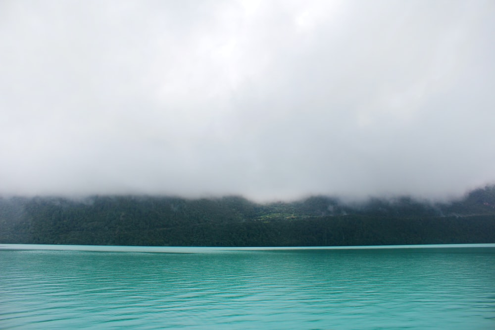 teal waters near land with mist