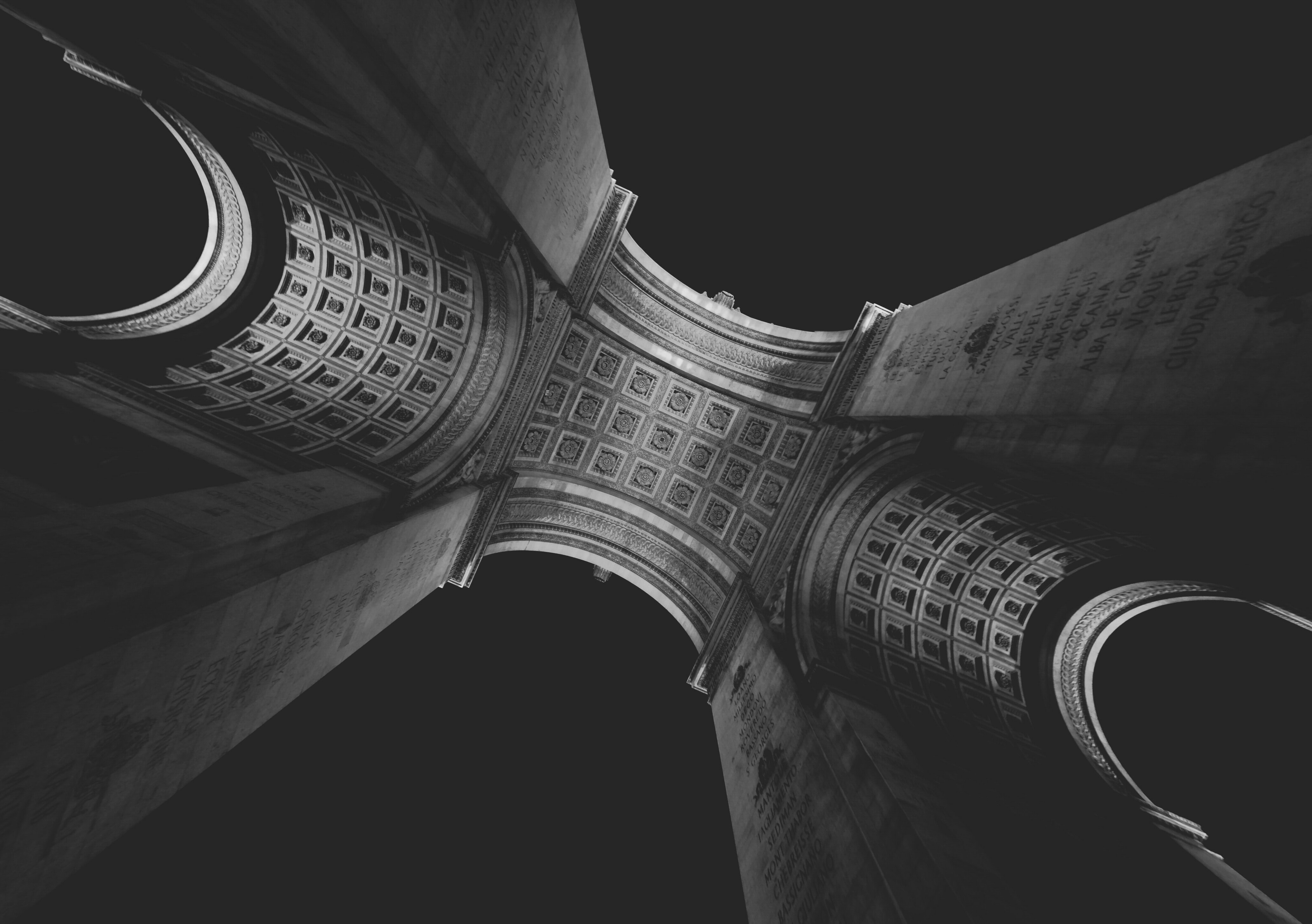 Looking up at the geometric architecture of the Arc De Triomphe in Paris, France