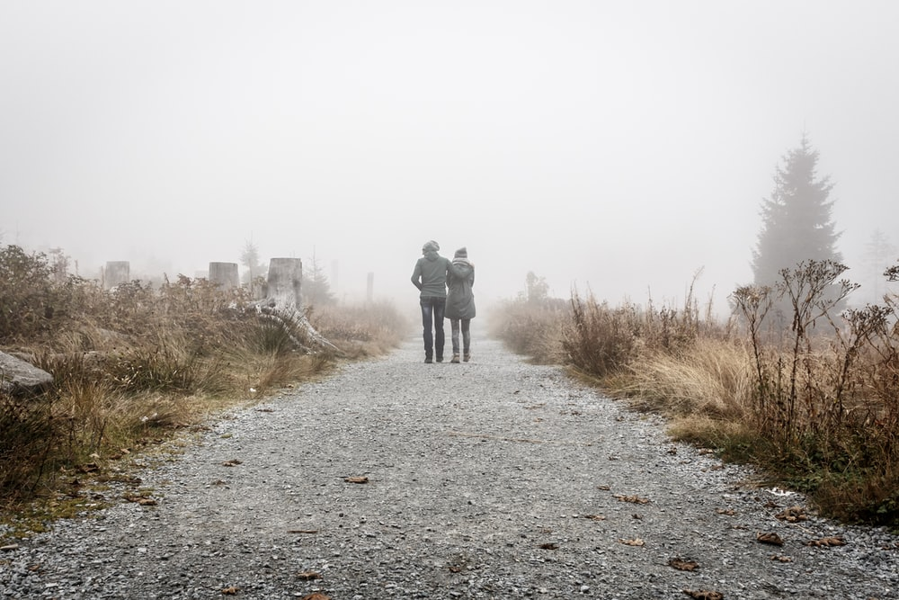 two person walking on gray road