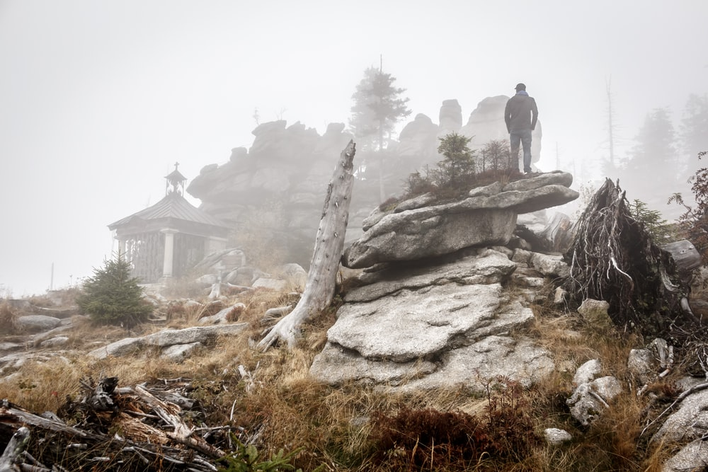 person standing on rock formation with fogs