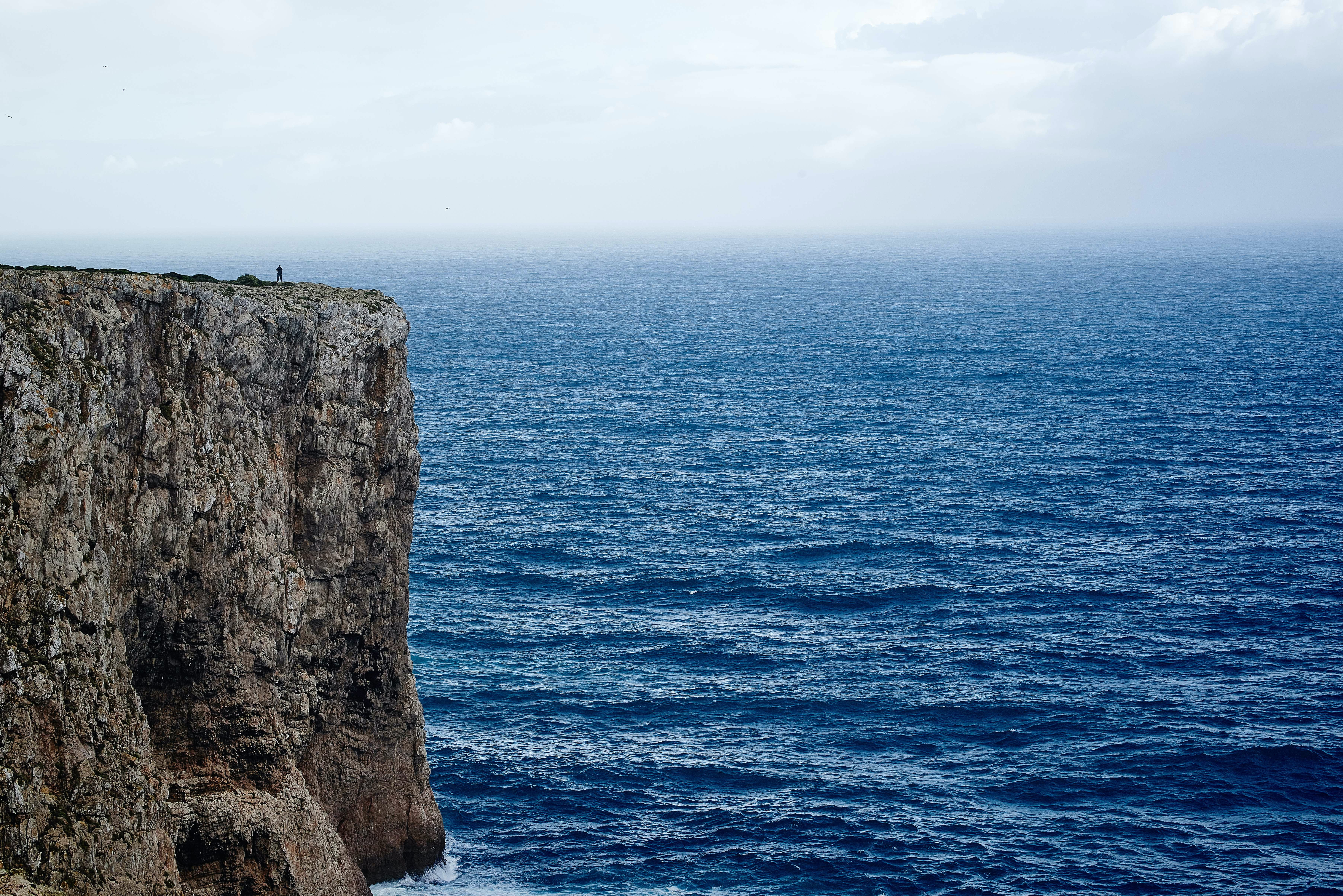 A rocky cliff overlooking a brilliant blue sea at Sagres