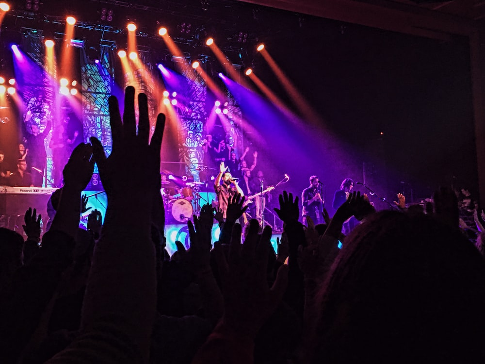 people raising their hands in front of stage