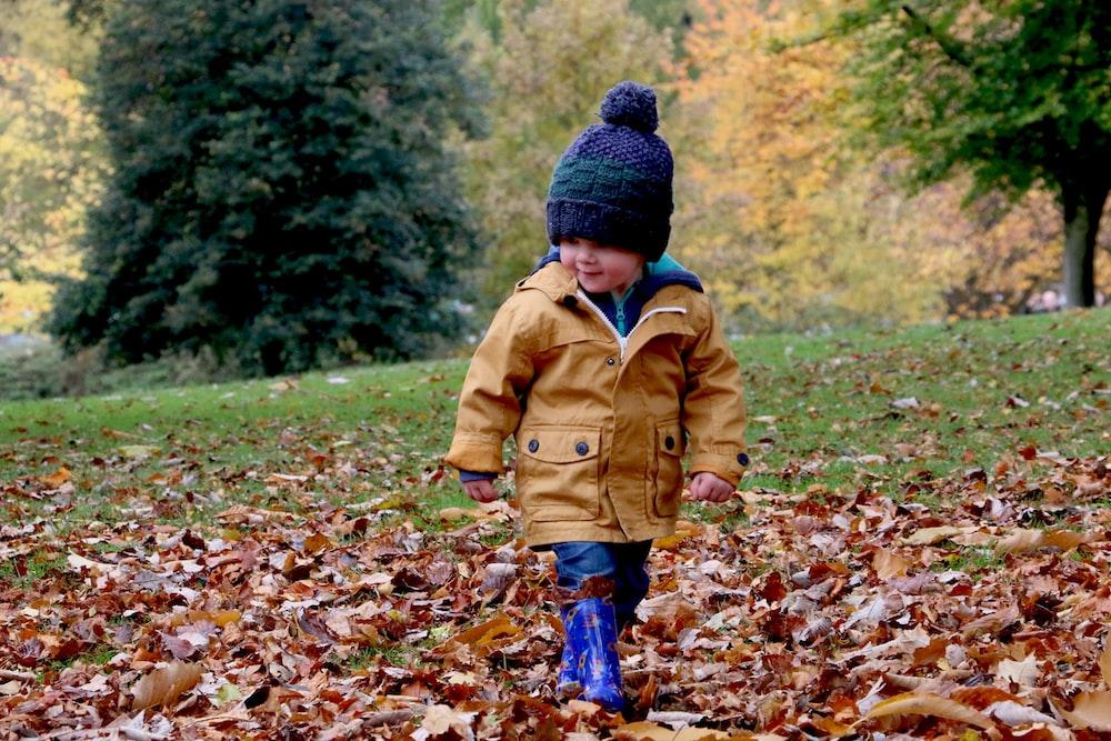 boy wearing orange bubble jacket walking on dry fallen leaves on ground