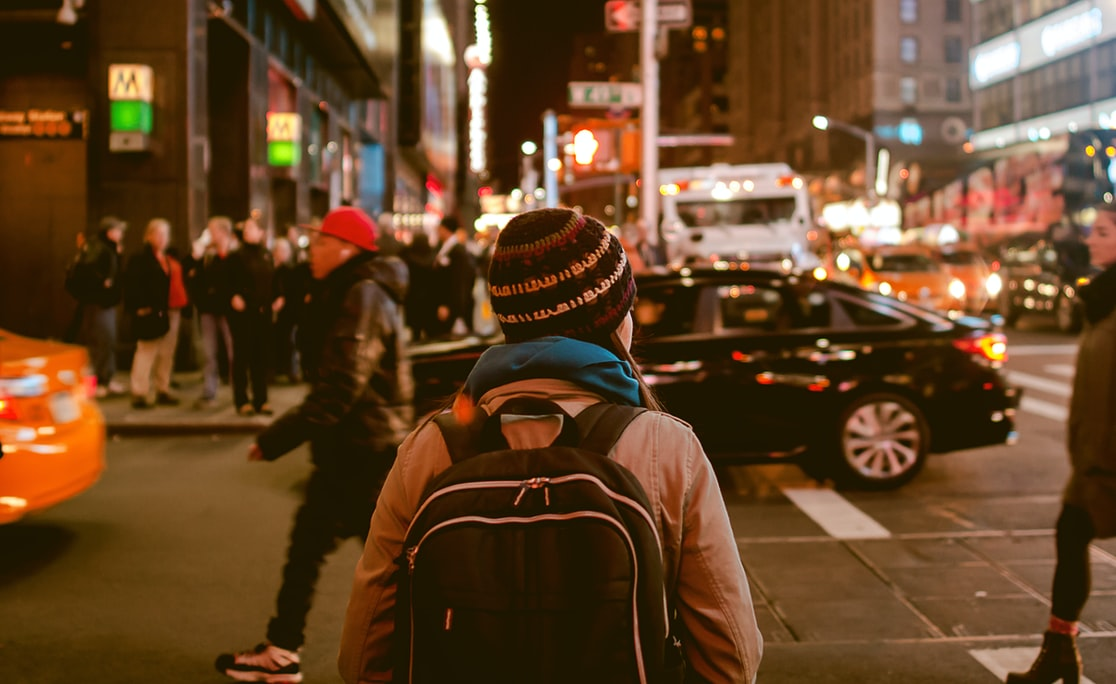 A photo of the back of a person's head. It looks like they are probably female. They are wearing a toque and a backpack and a jacket. It's night time and they are on a street with lots of lights and other people around.