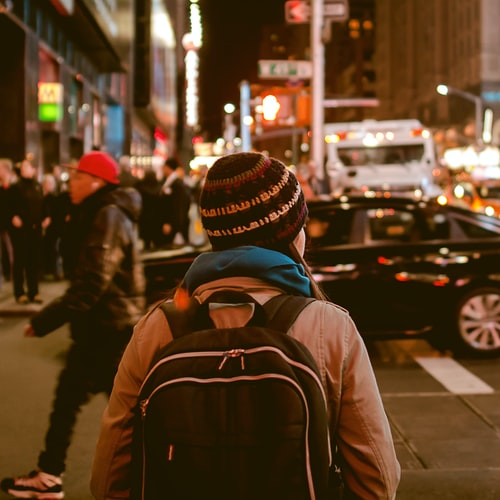 back view of woman wearing a backpack and beanie waiting to cross the road on a busy street at night in New York City, USA