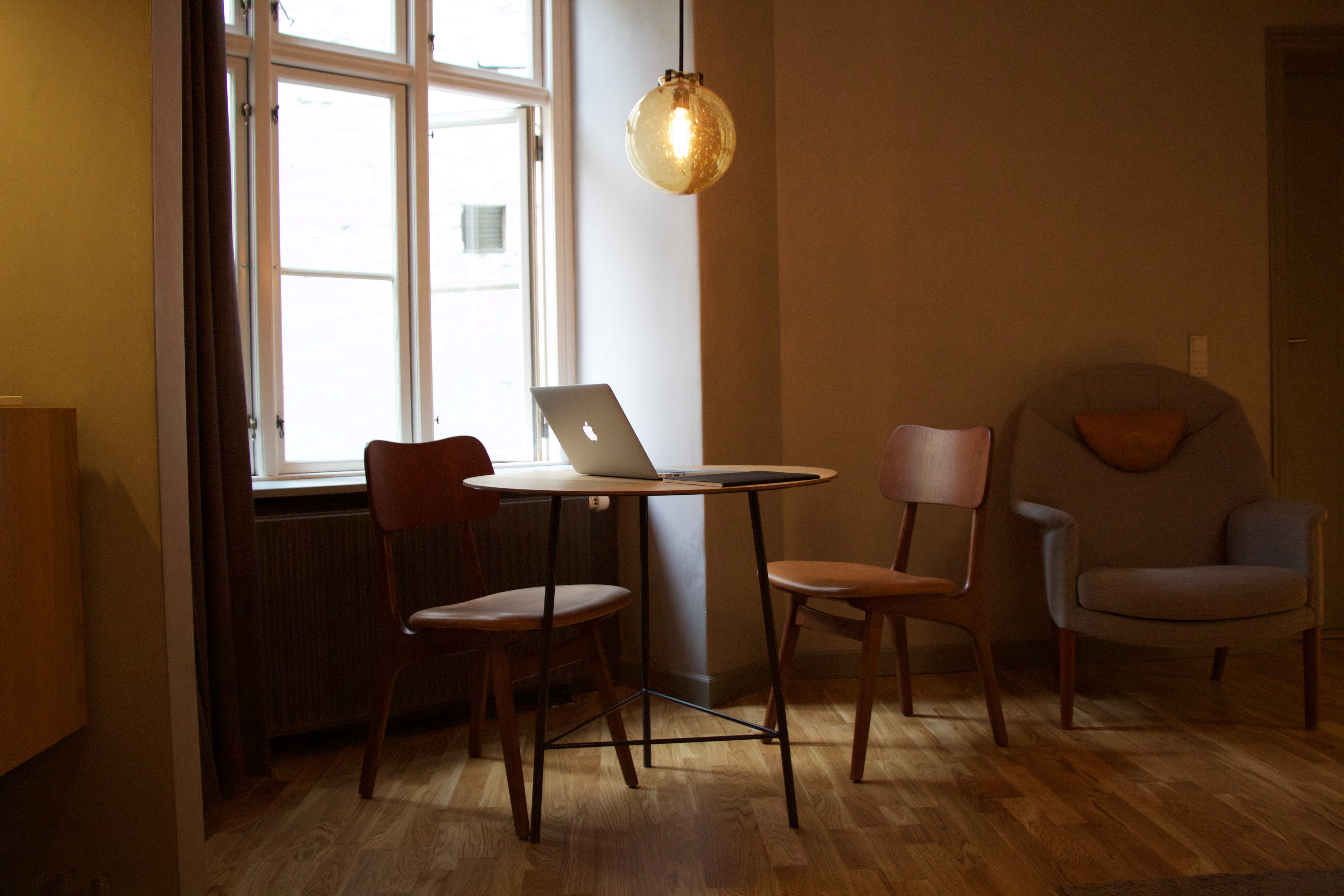 A MacBook on a small round table in a cosy living room