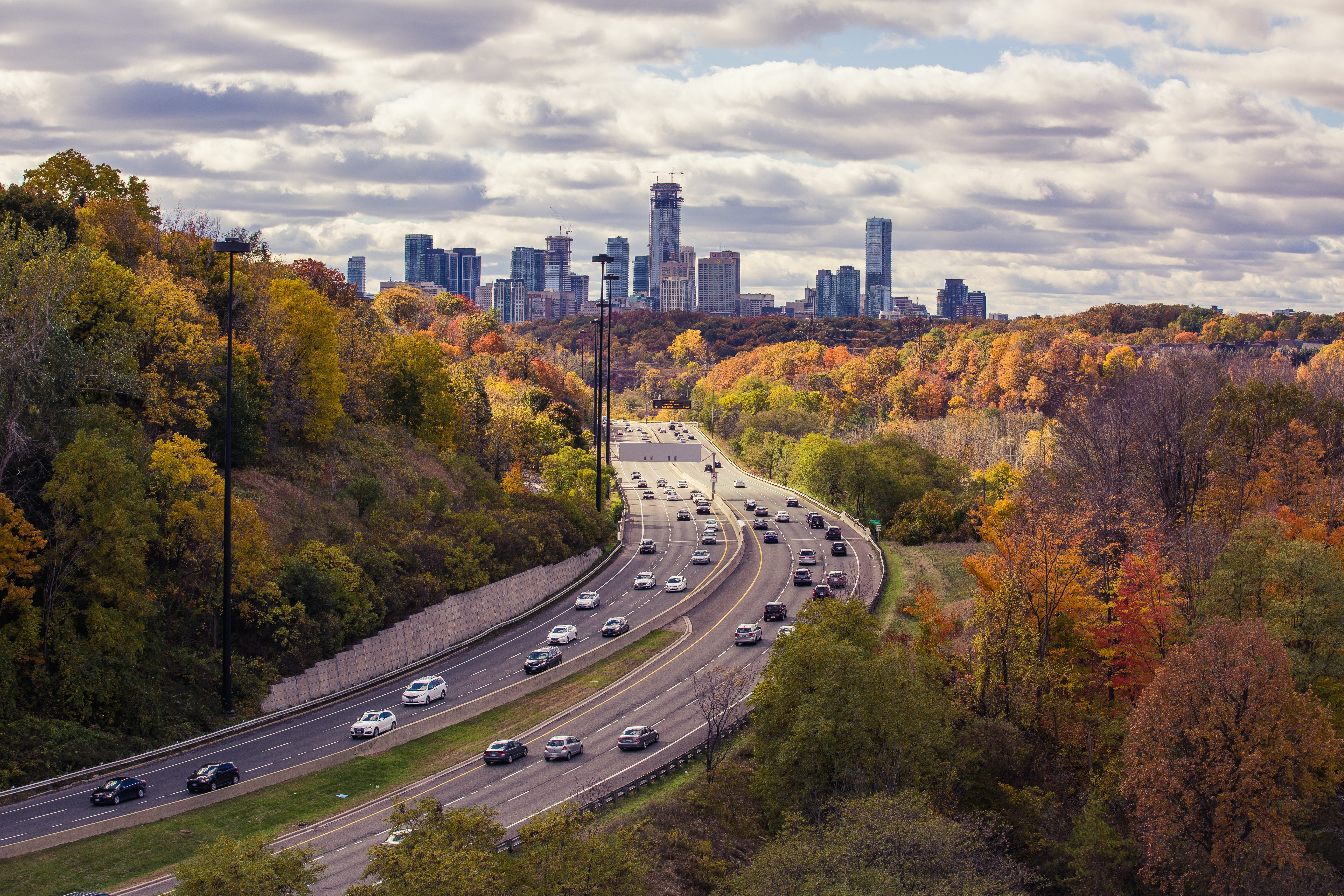 Long shot of busy daytime highway traffic with autumnal trees at Leaside Bridge