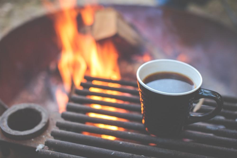 black ceramic mug near fire