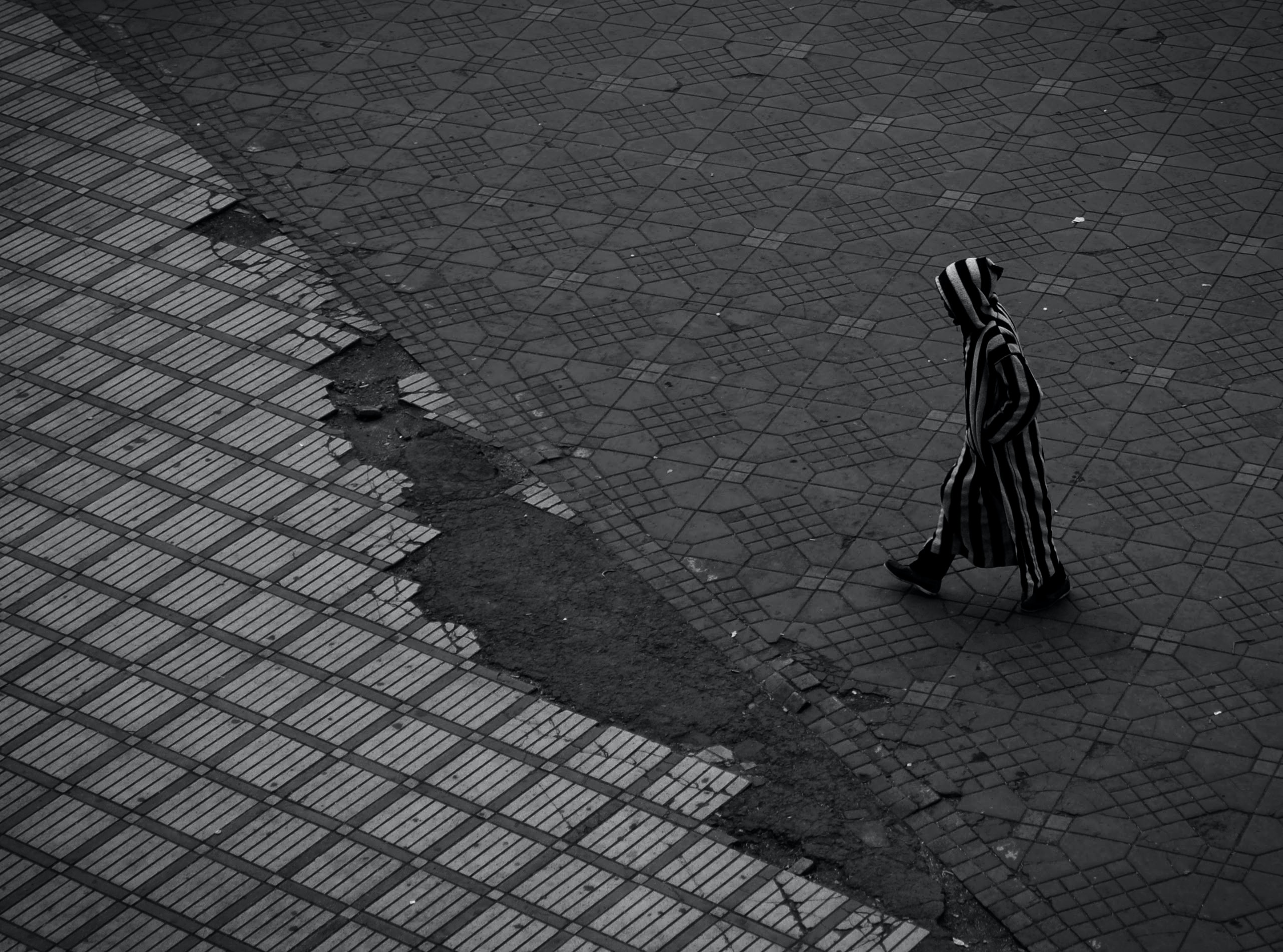 An urban person walking on a sidewalk in black and white, Marrakesh