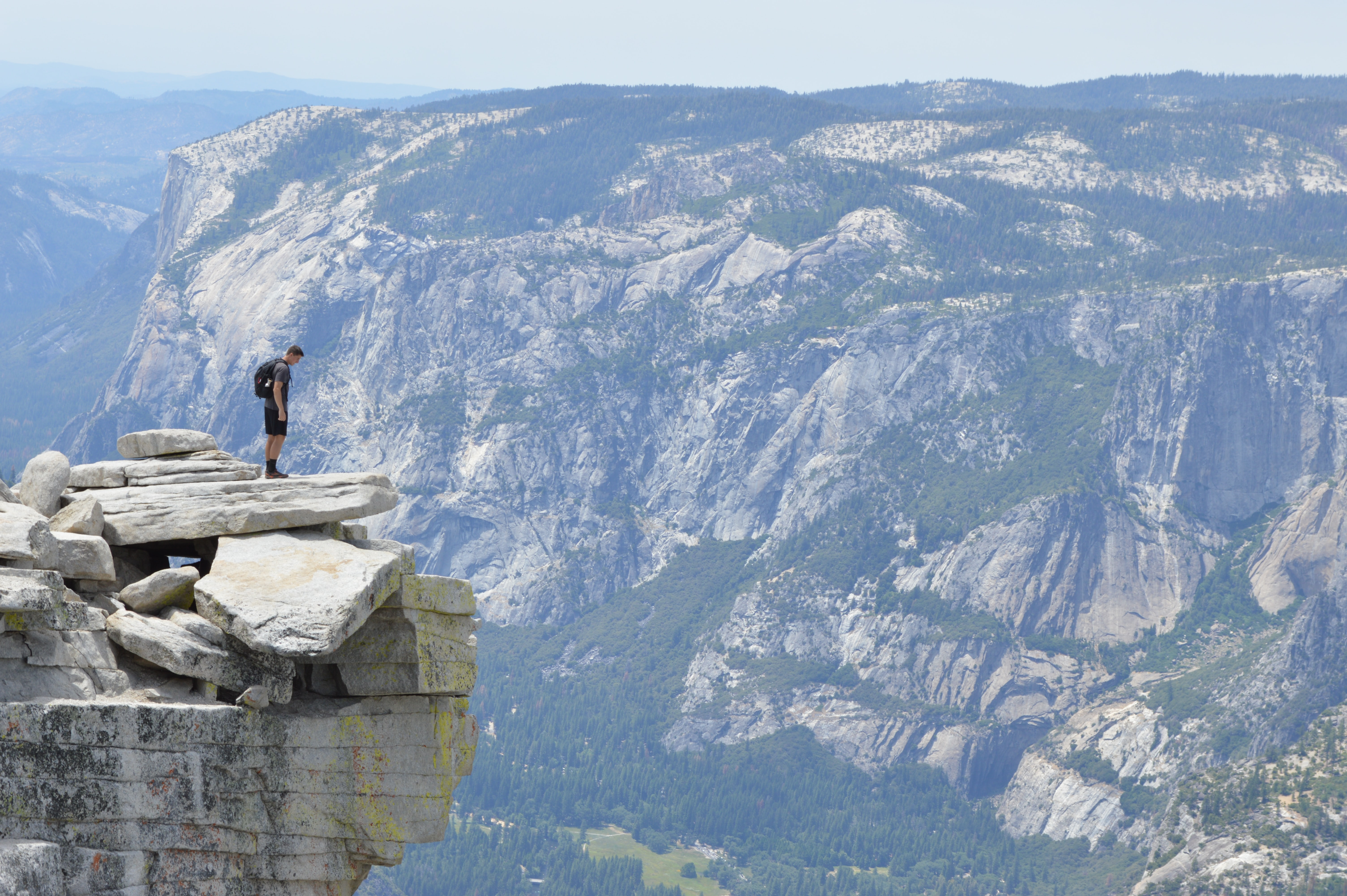 A male hiker looking down a precipice over the deep valley