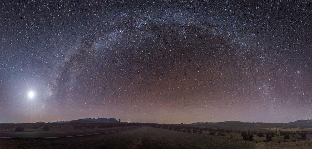 gray concrete road under sky full of stars