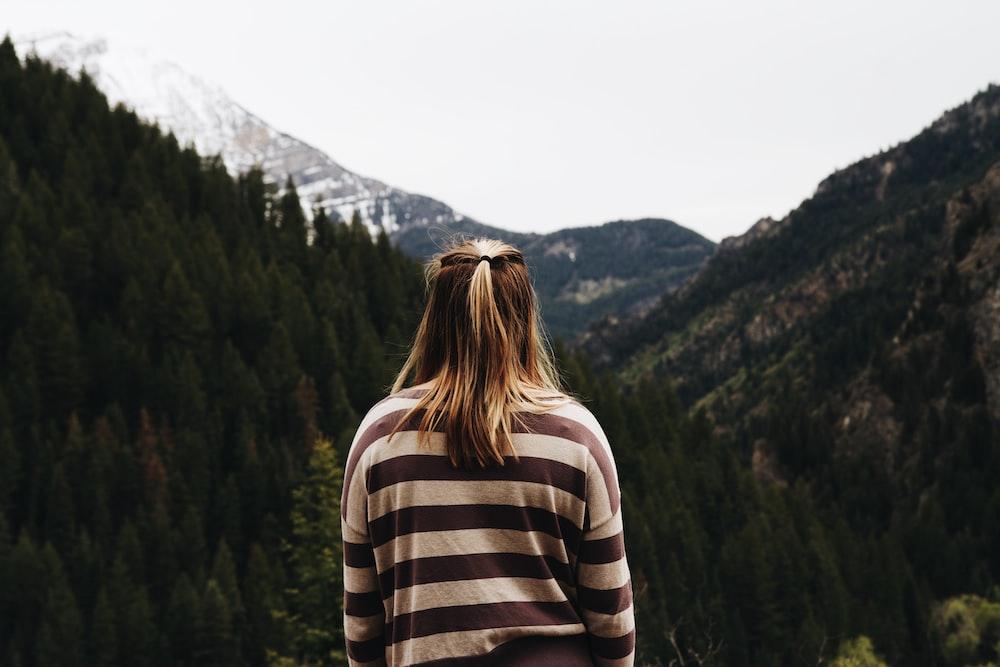 woman wearing striped long-sleeved shirt facing mountains
