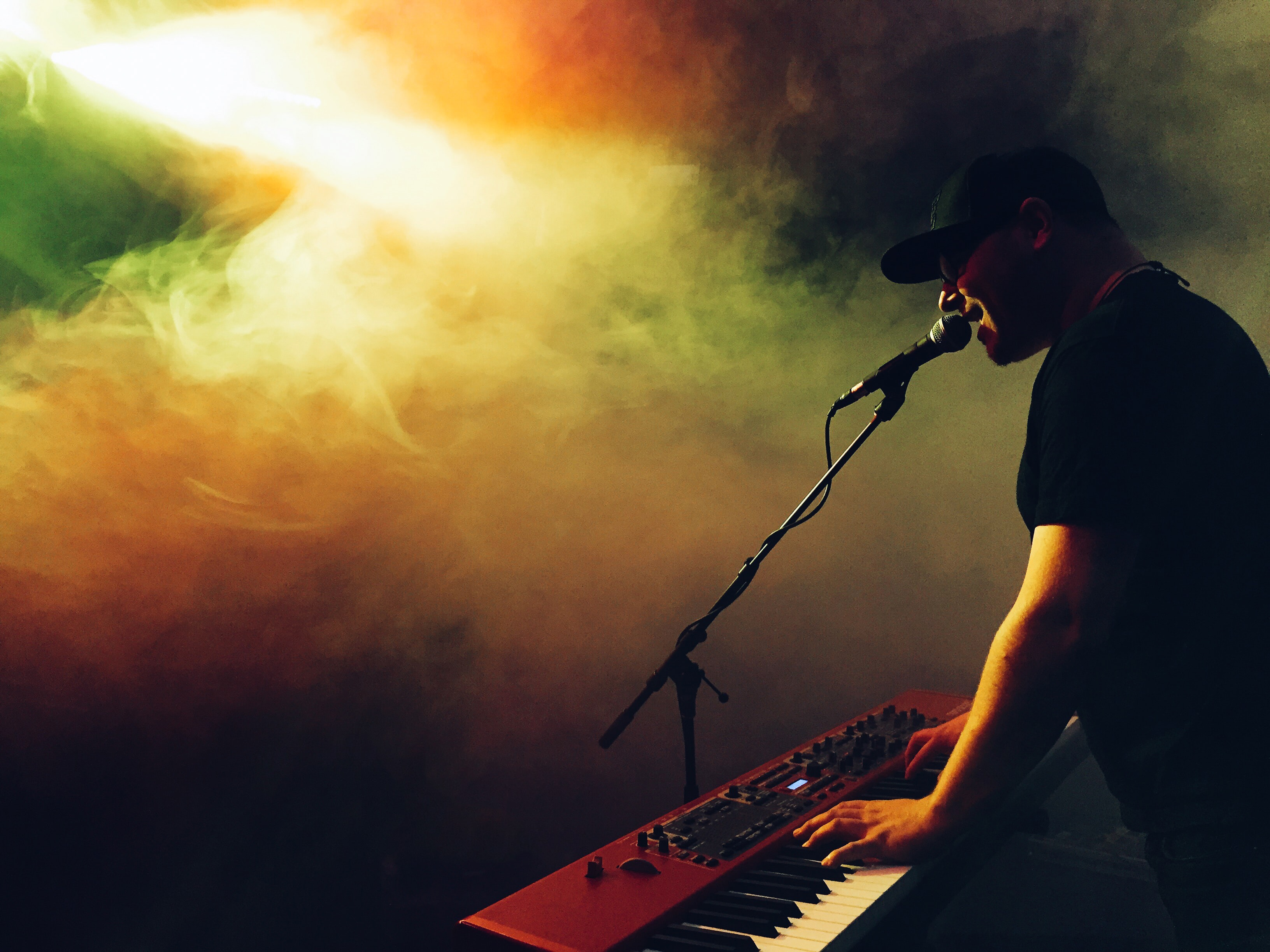 A man in a hat playing the keyboard and singing into a microphone with colorful smoke in front of him