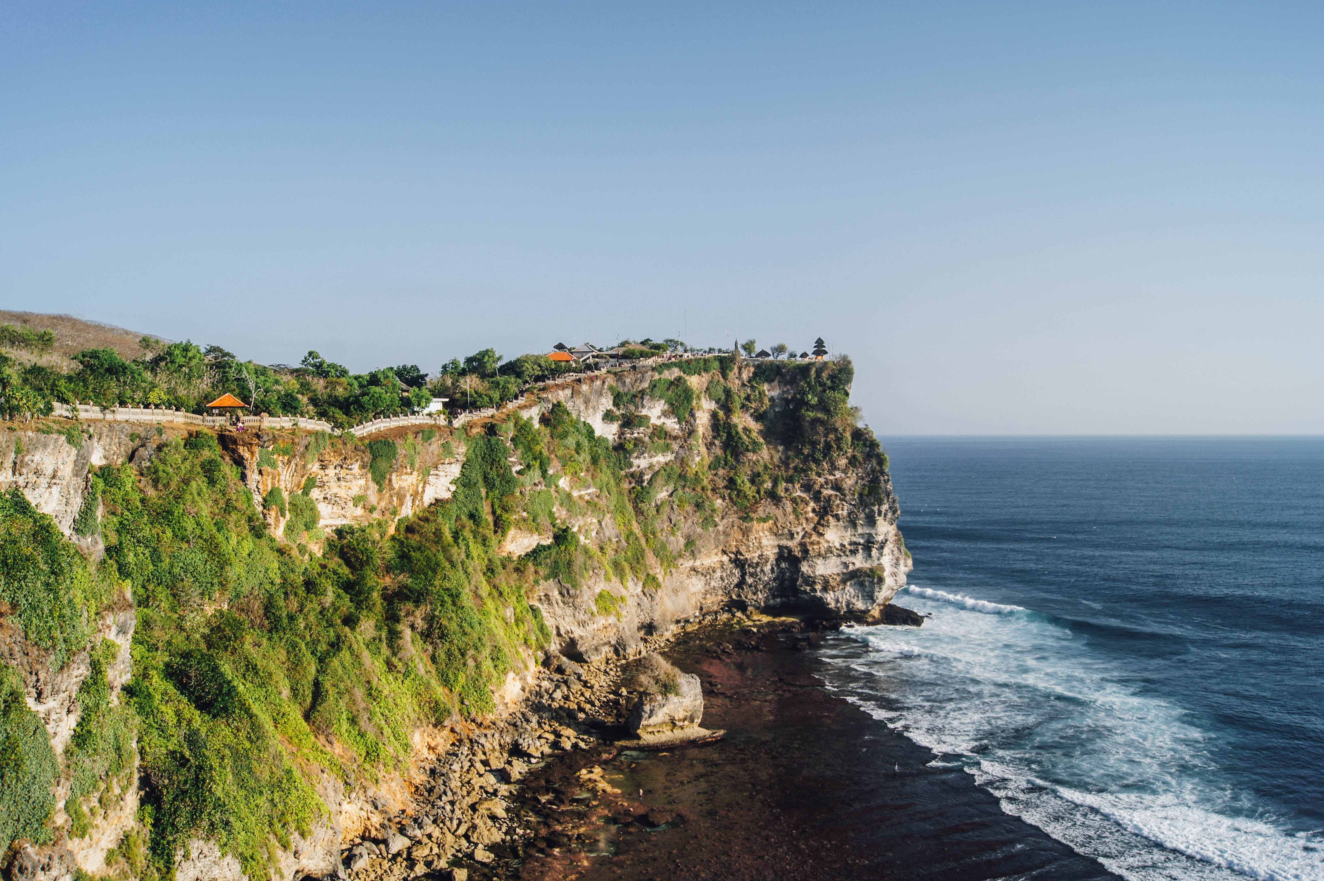 Scenic beach on a cliff features nature's finest rocks, trees and foliage with sea underneath