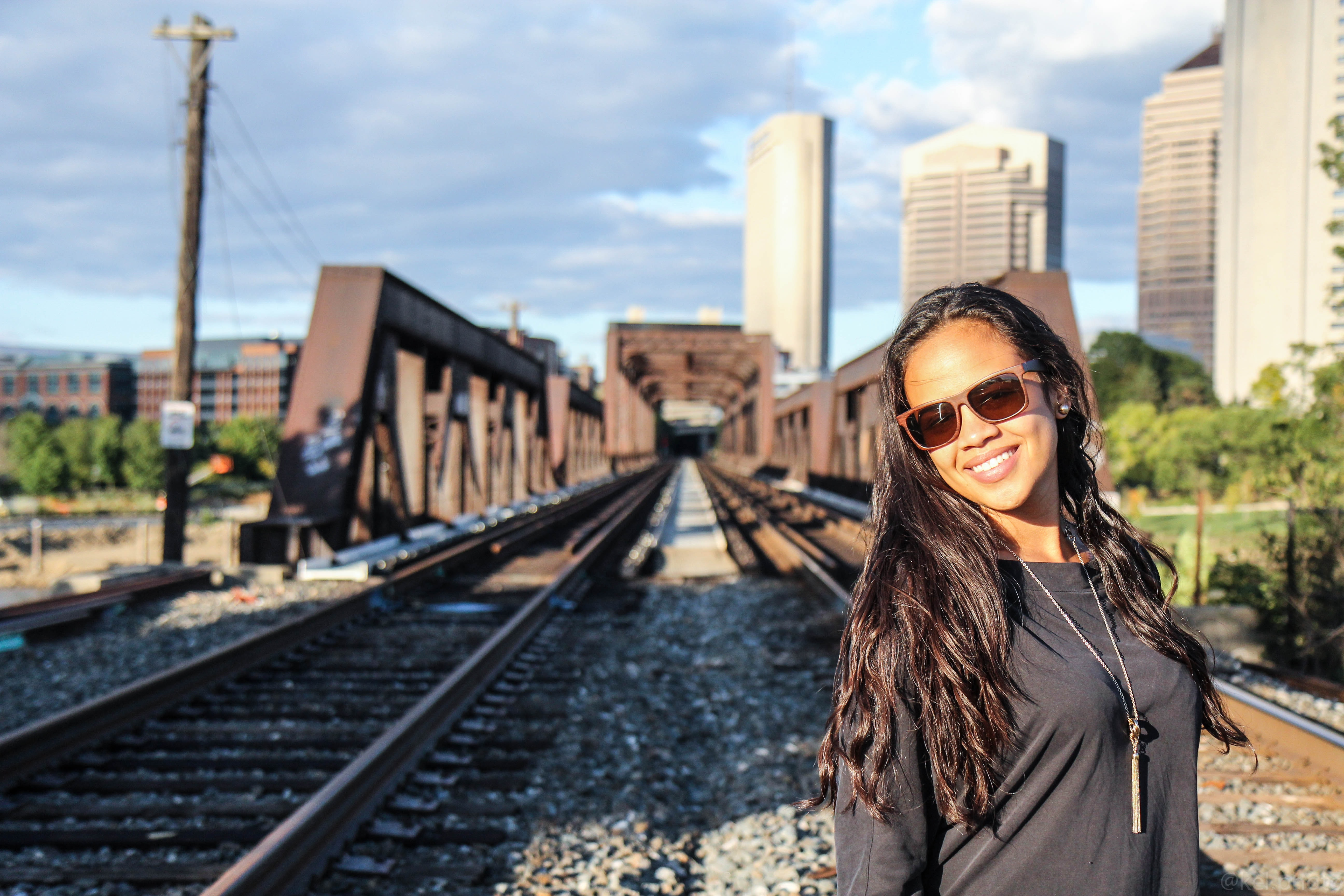 Woman in sunglasses with a long necklace smiles in front of train tracks in the city