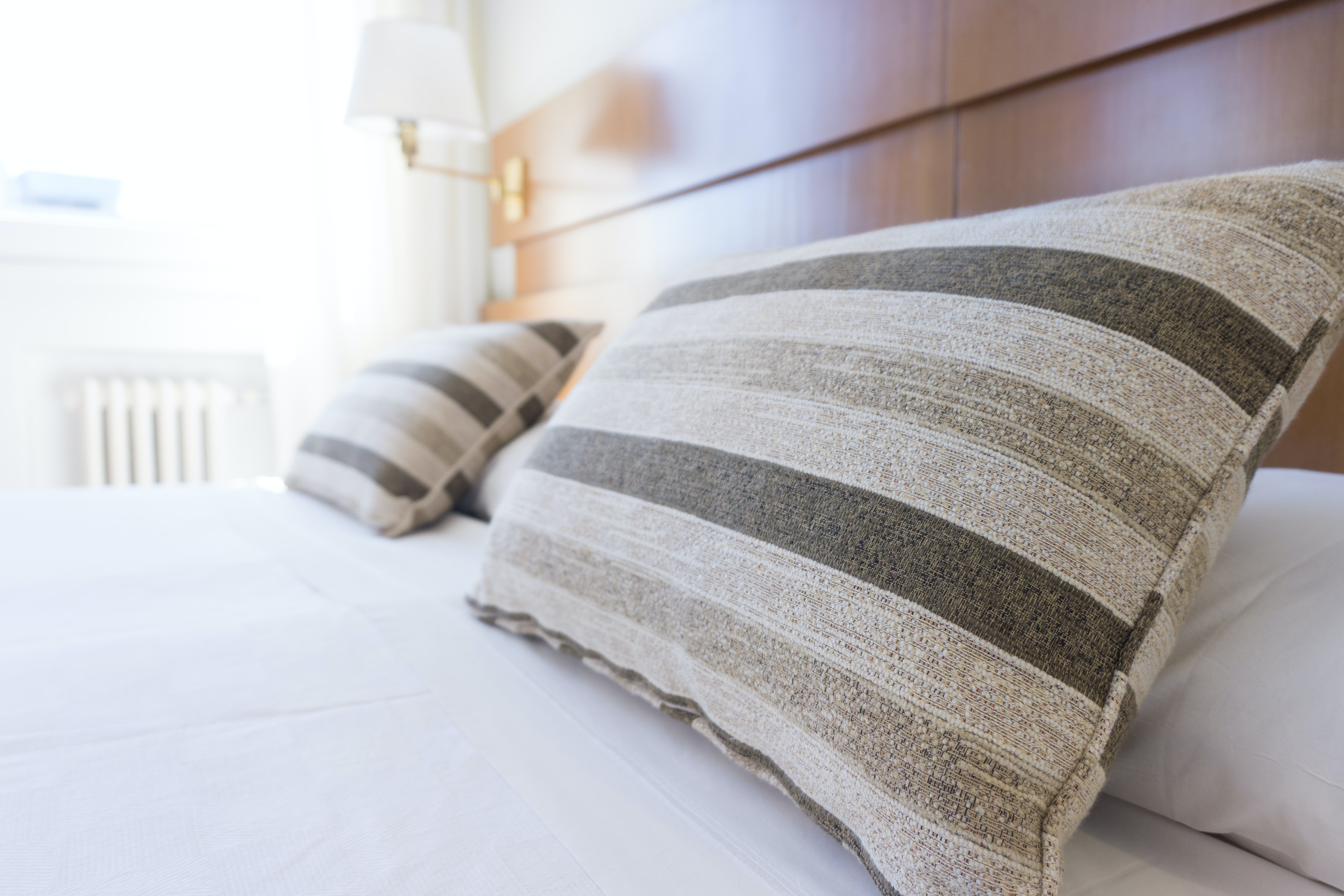 gray and black throw pillow on bed