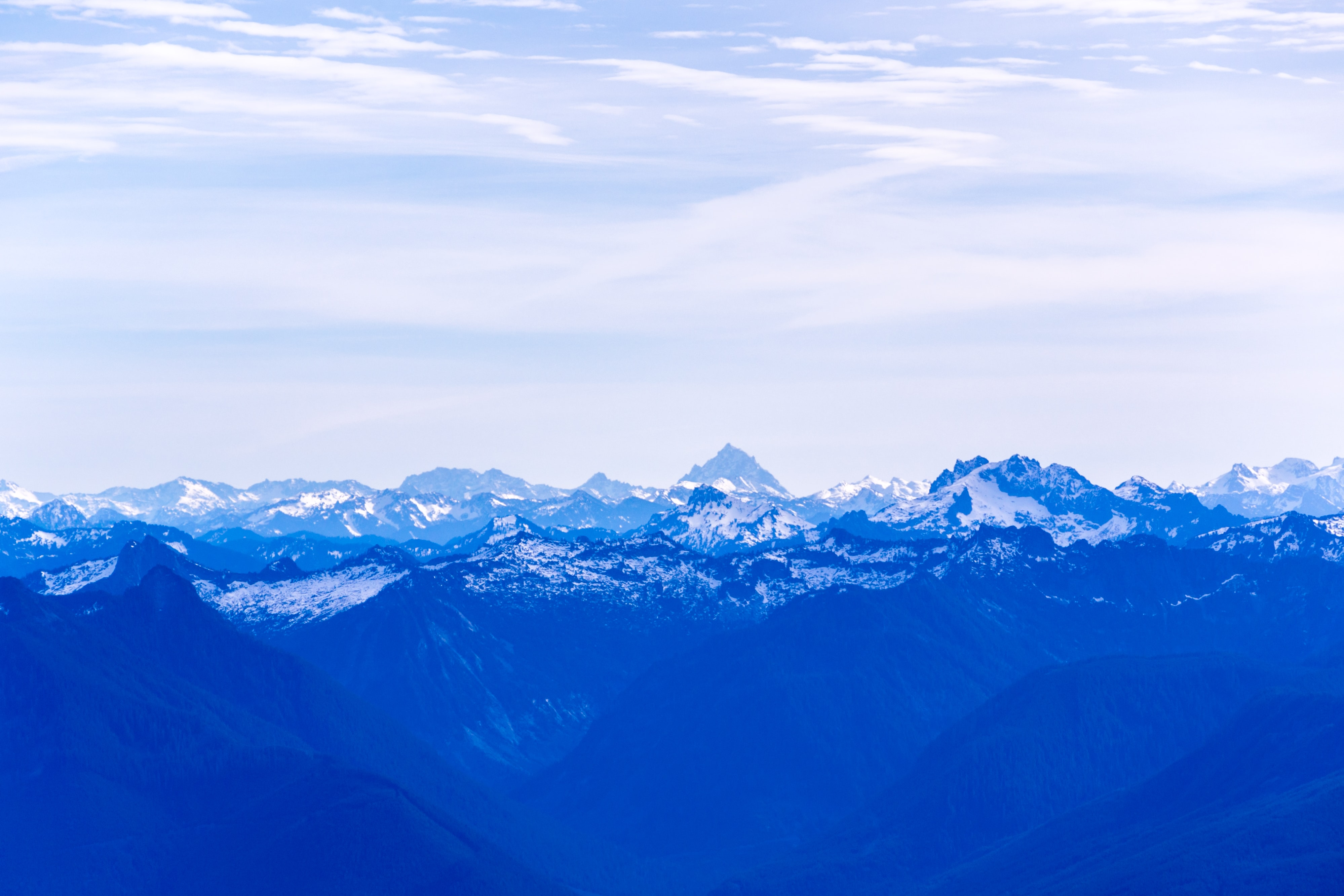 The sharp peak of Mount Pilchuck on the horizon rising up above a hazy mountain range