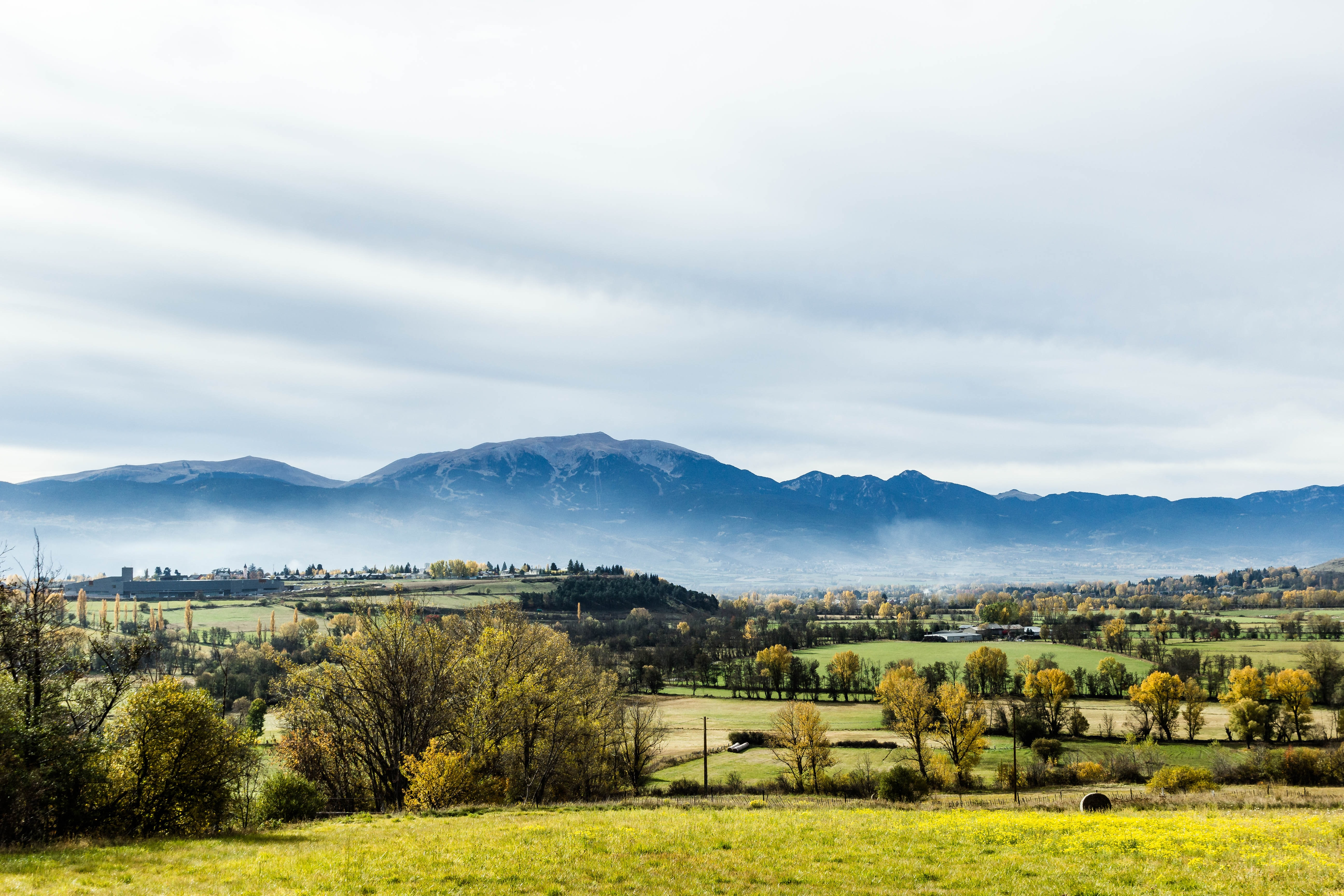 A woody countryside landscape with a snow-capped mountain towering over the village