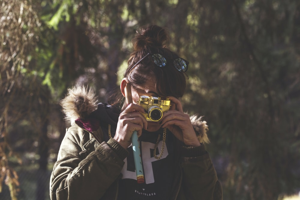woman in black jacket holding green and white camera