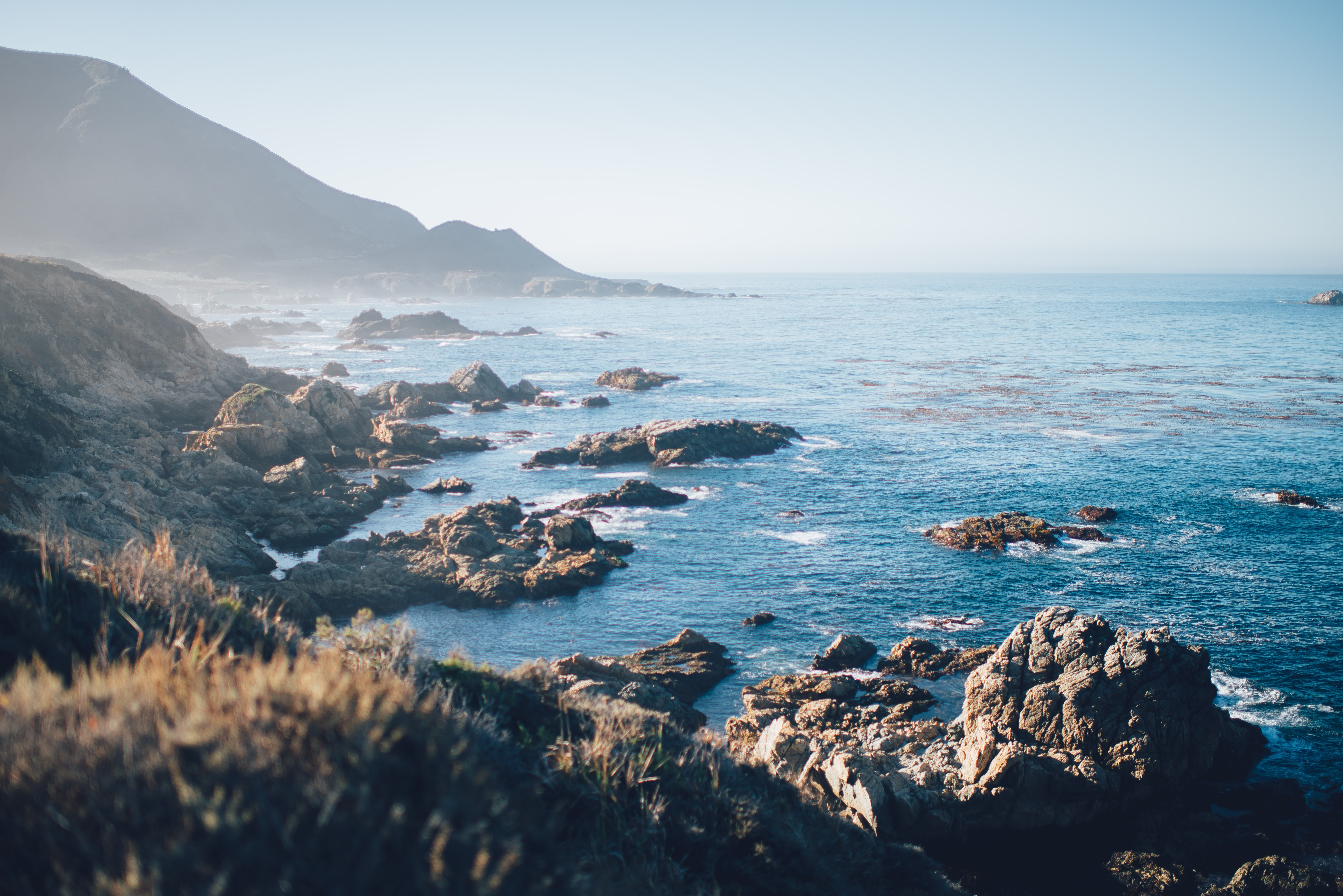 A rocky coastline, with mountains in the background overlooking the blue sea at Bixby Creek Bridge