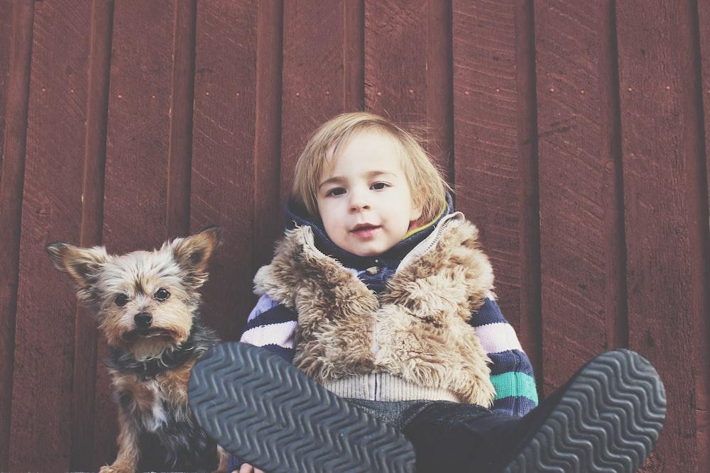 niño sentado en el piso brside perro