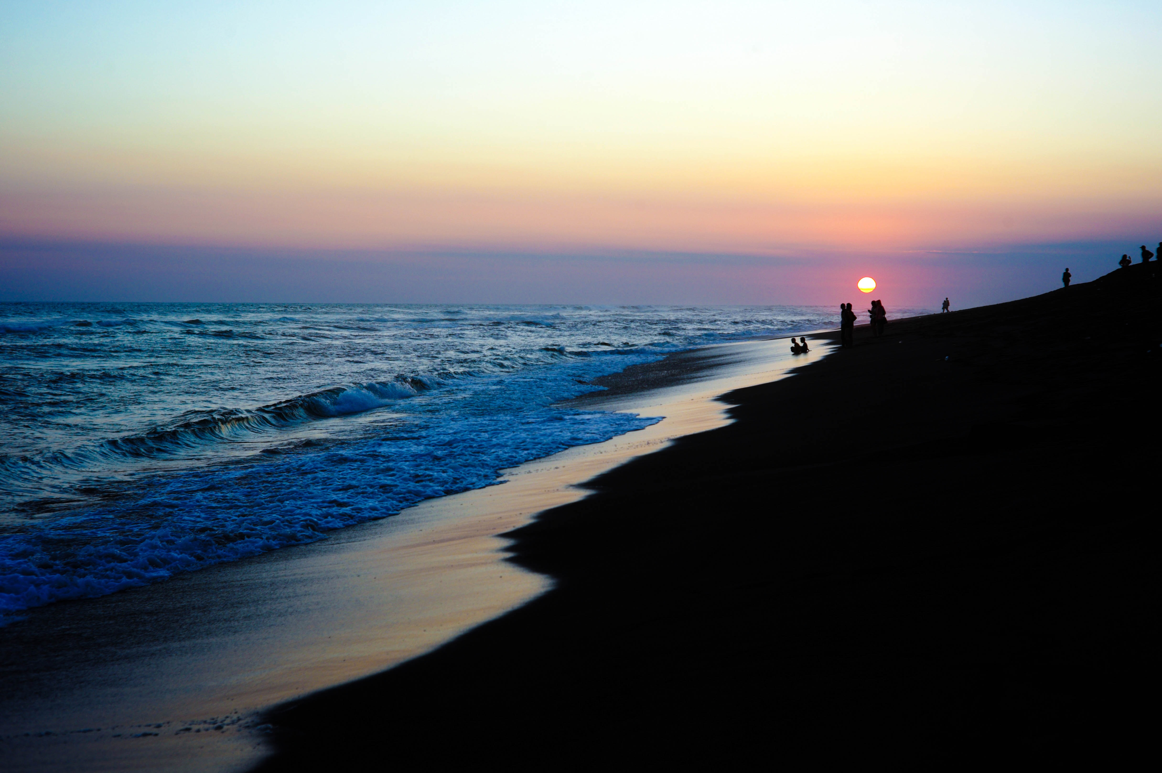 photography of silhouette of people on seashore