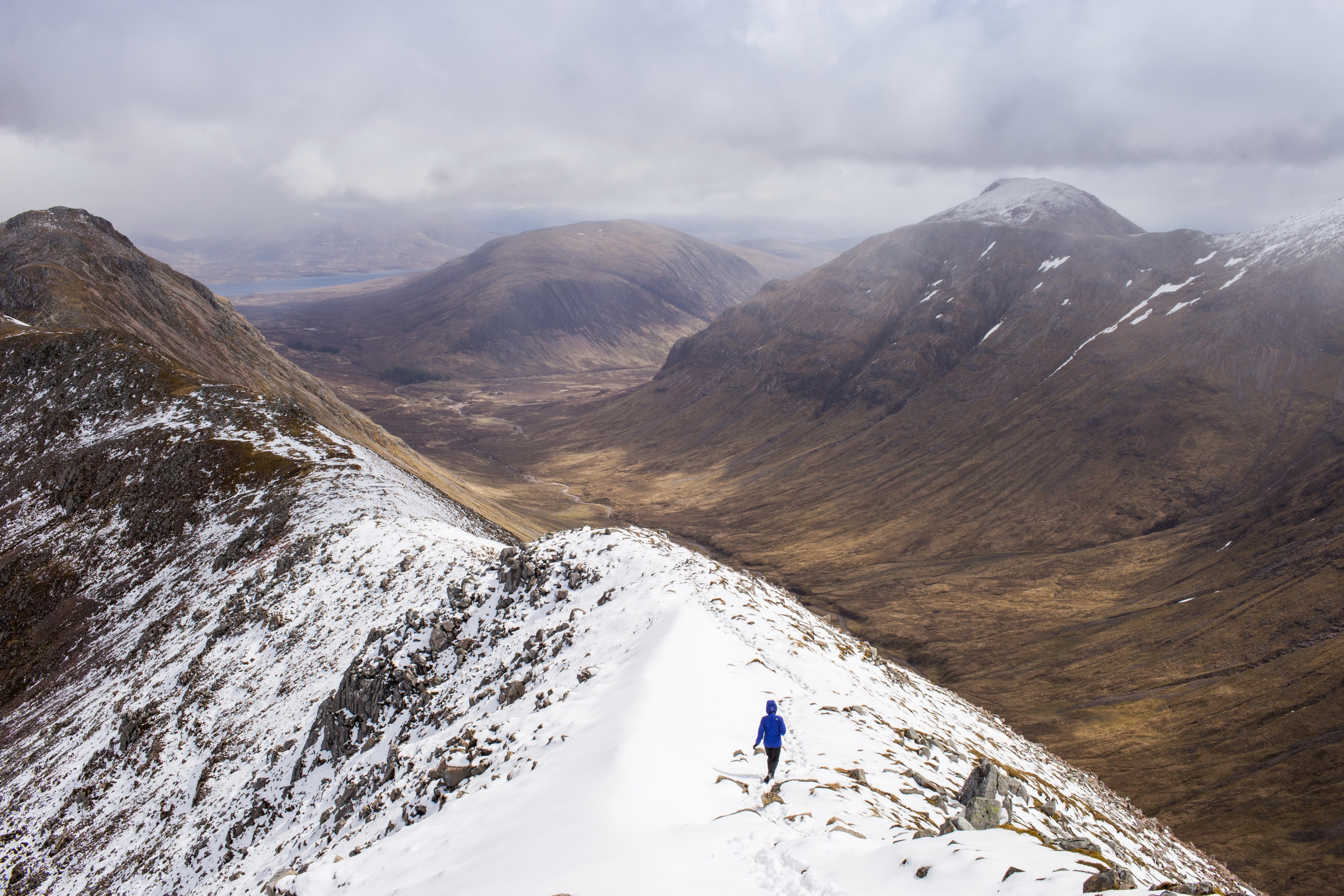 Mountain range under clouds with hiker walking along the top in snow