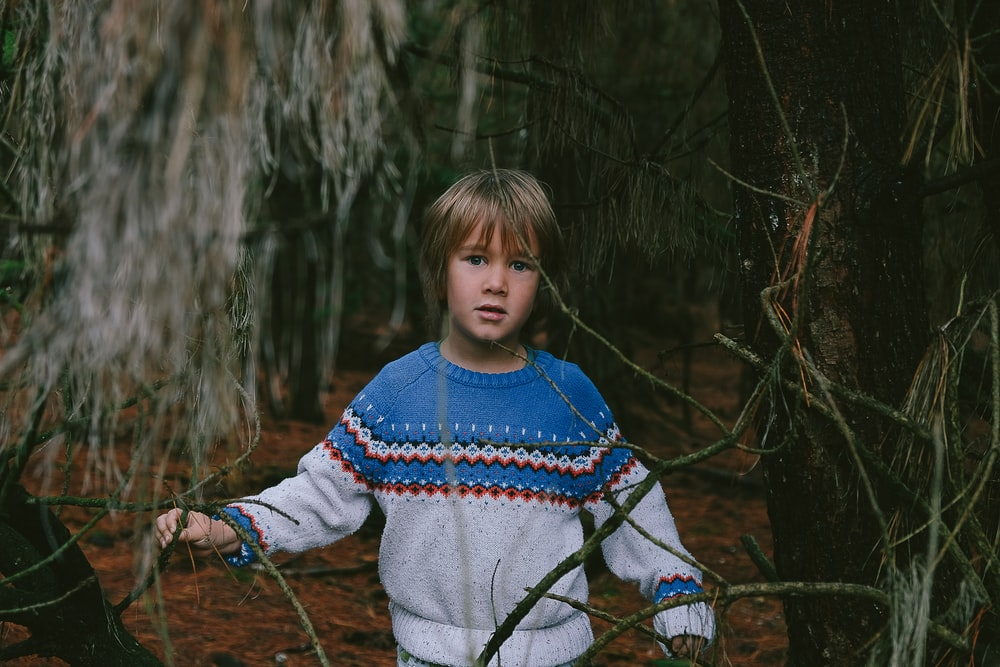 boy standing near tree