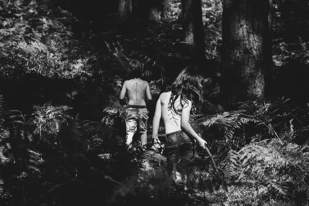 grayscale photography of two topless persons standing at the forest during day