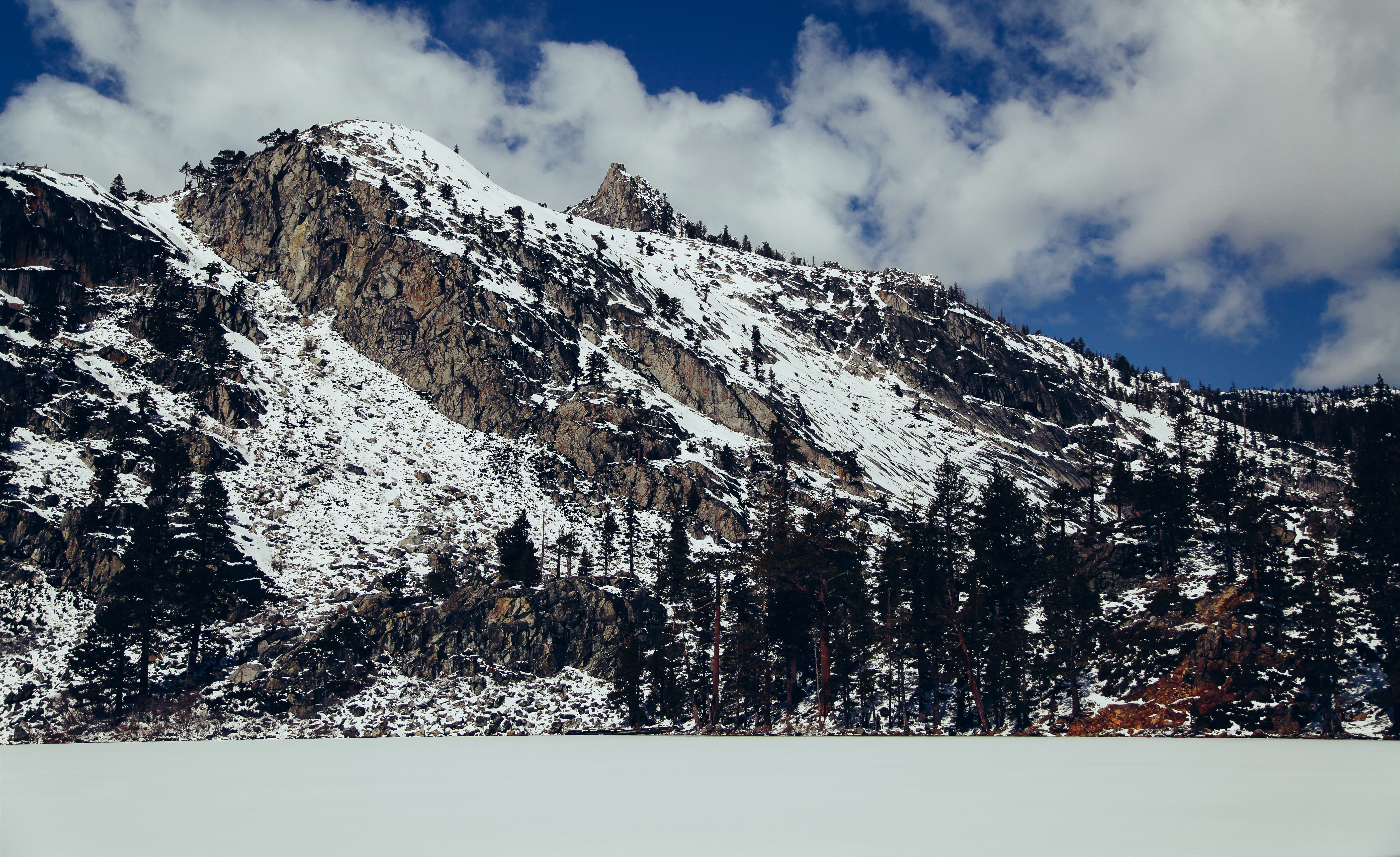 The milky surface of a lake next to a snow-covered mountain slope