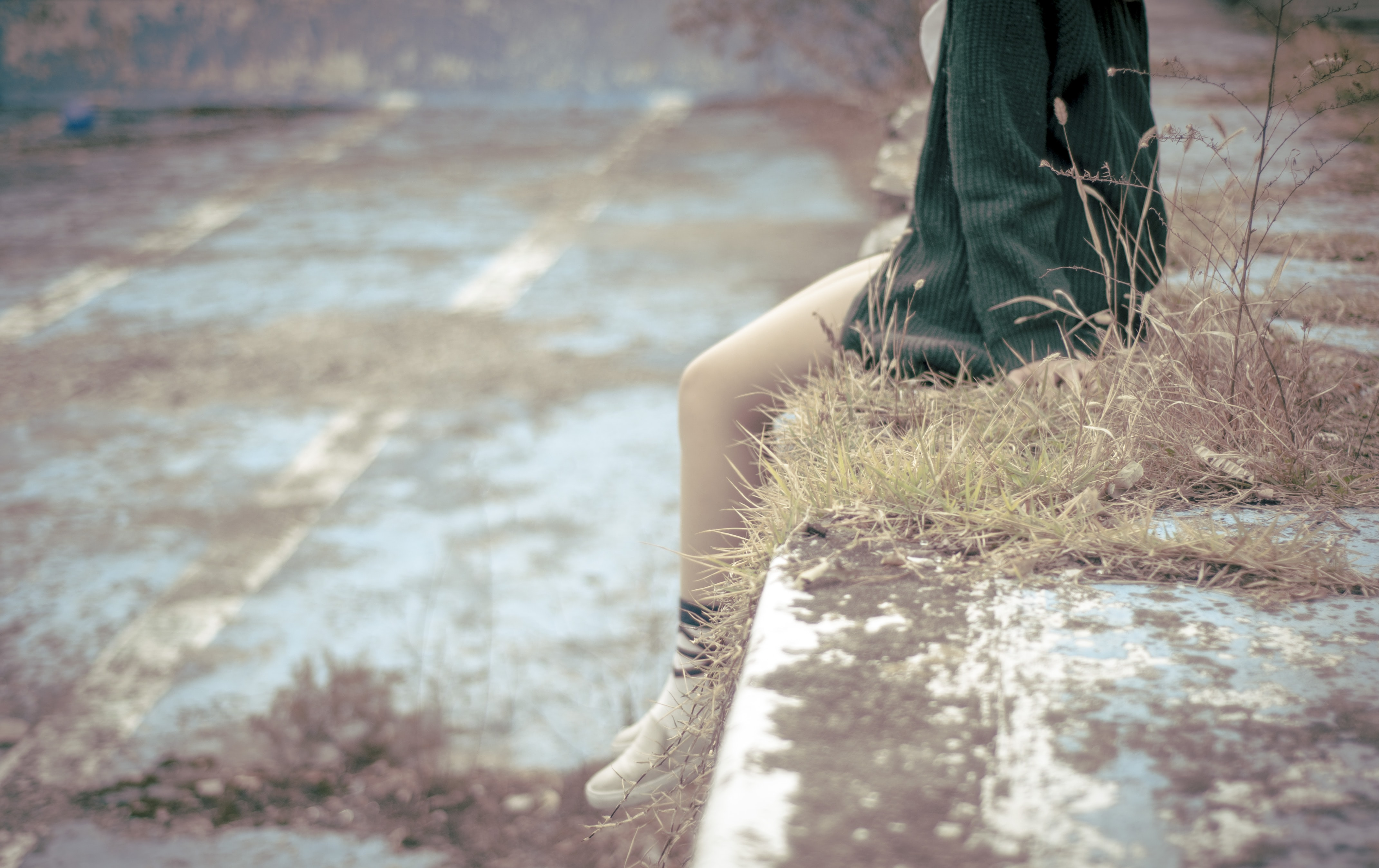 woman sitting on concrete barrier