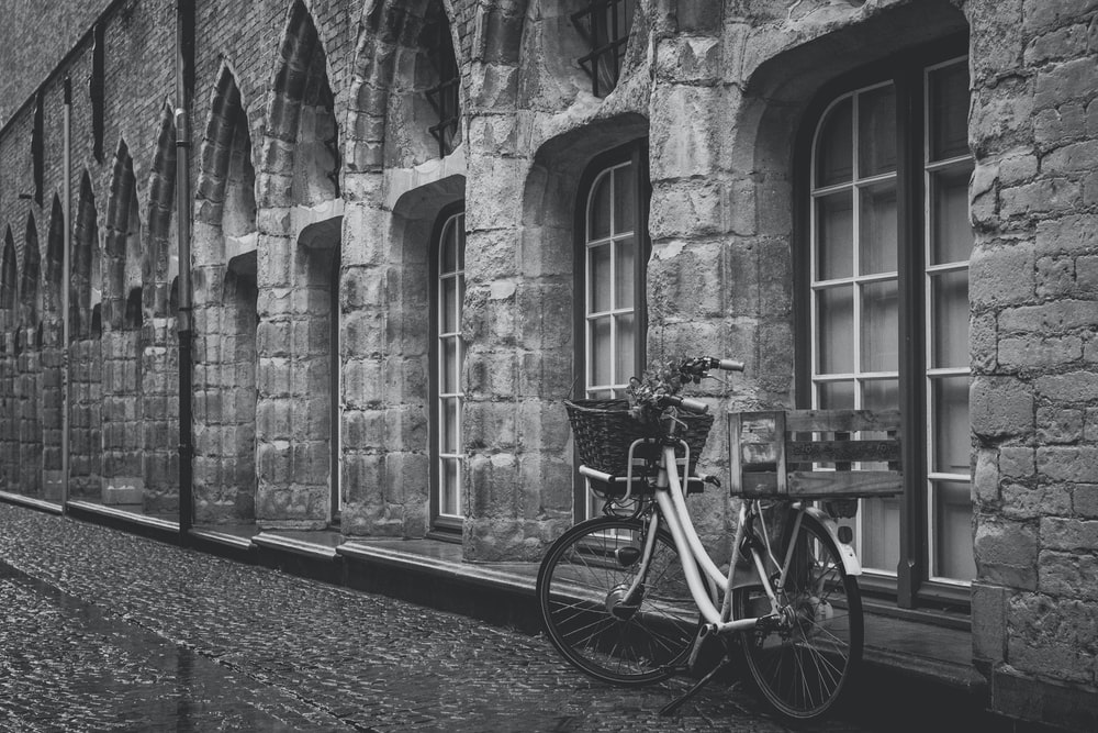 grayscale photo of bike parked beside building