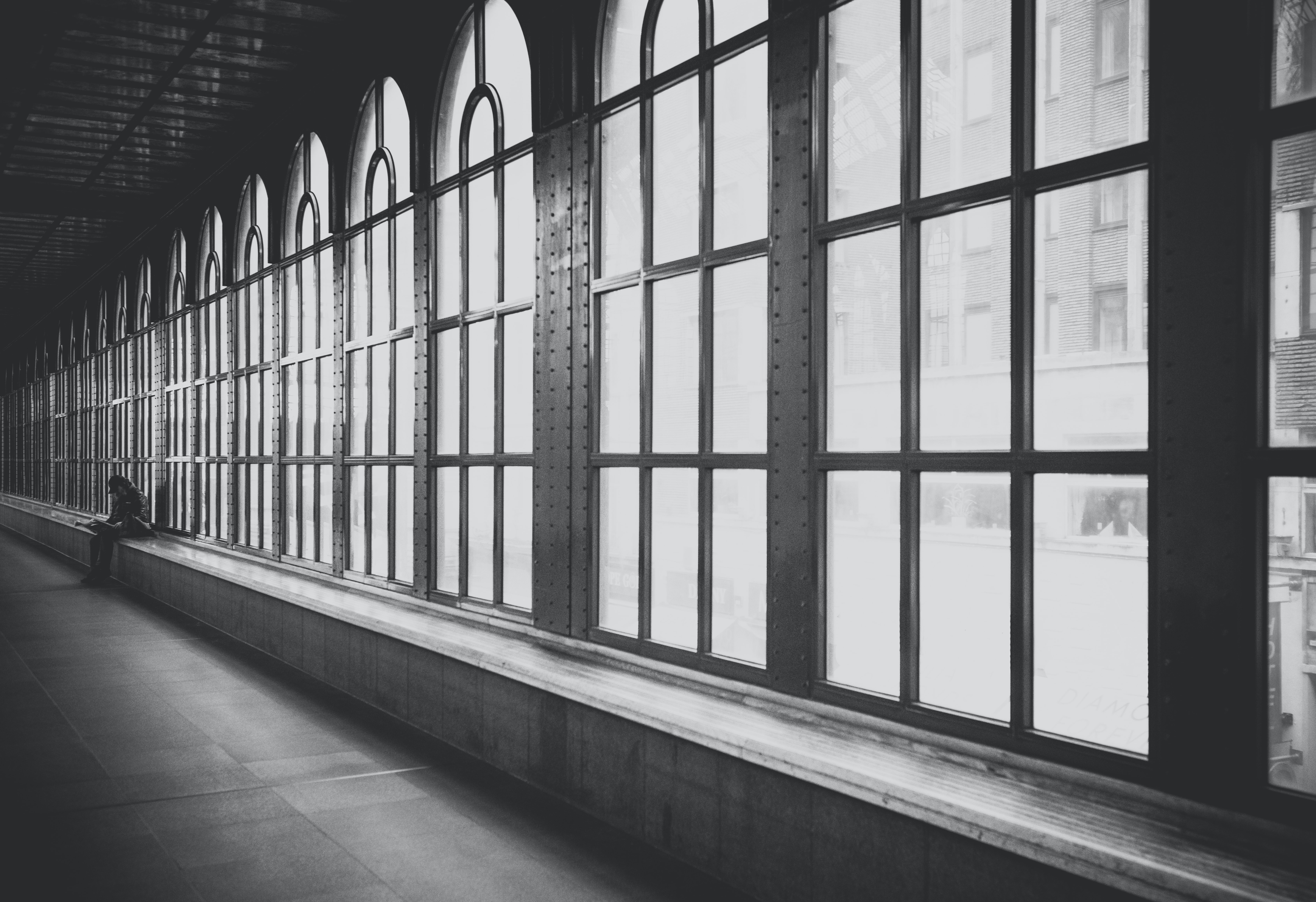 Black and white shot of hallway interior with large windows with person sitting