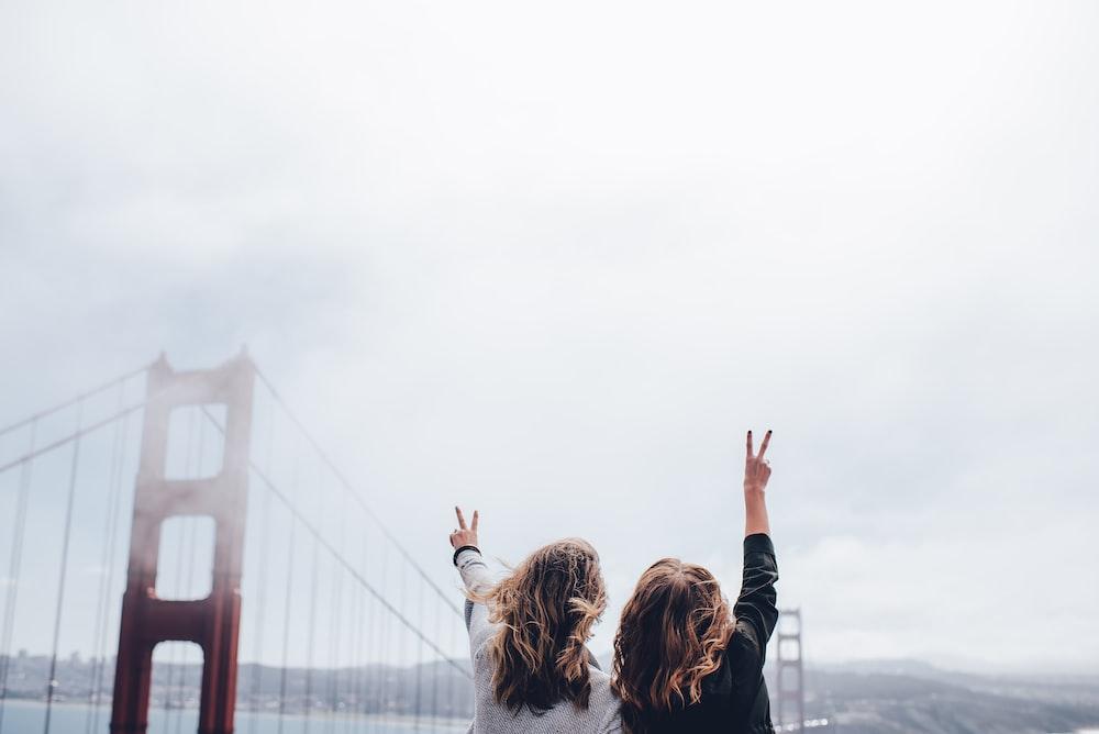 two women making peace sign near the Golden Gate bridge