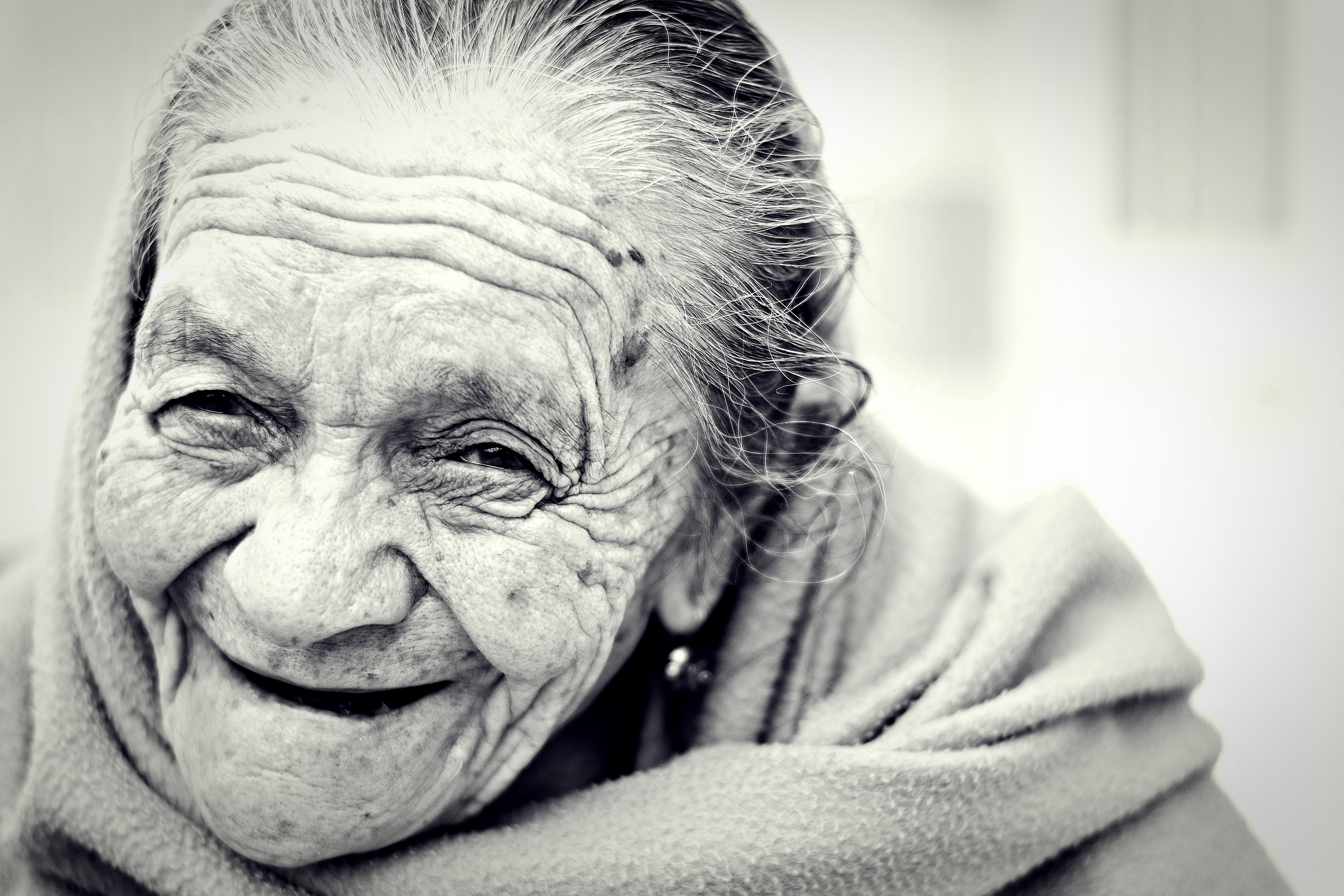 Elderly woman with care worn face laughs in black and white photo