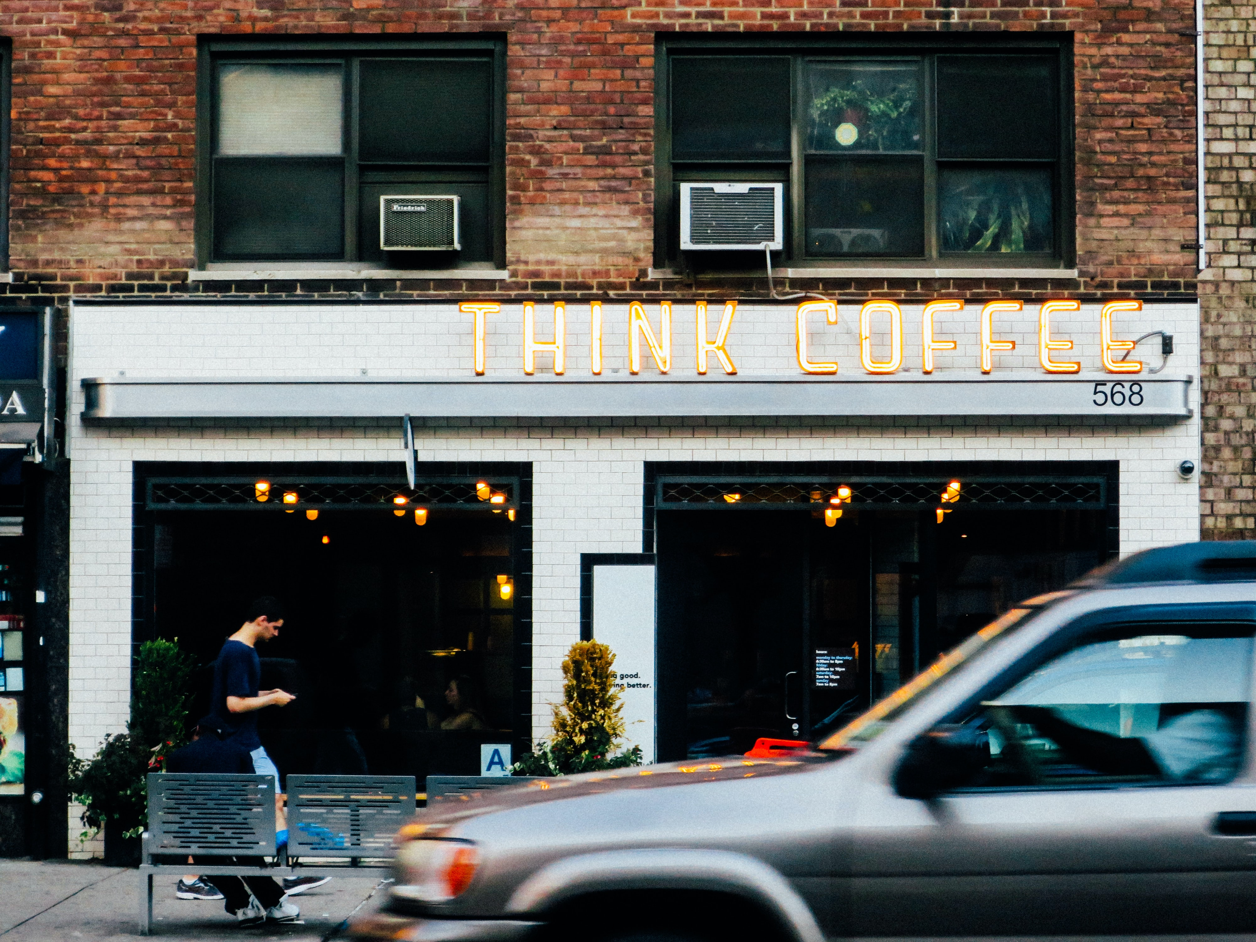 "A yellow ""Think Coffee"" neon over the entrance to a coffee shop"