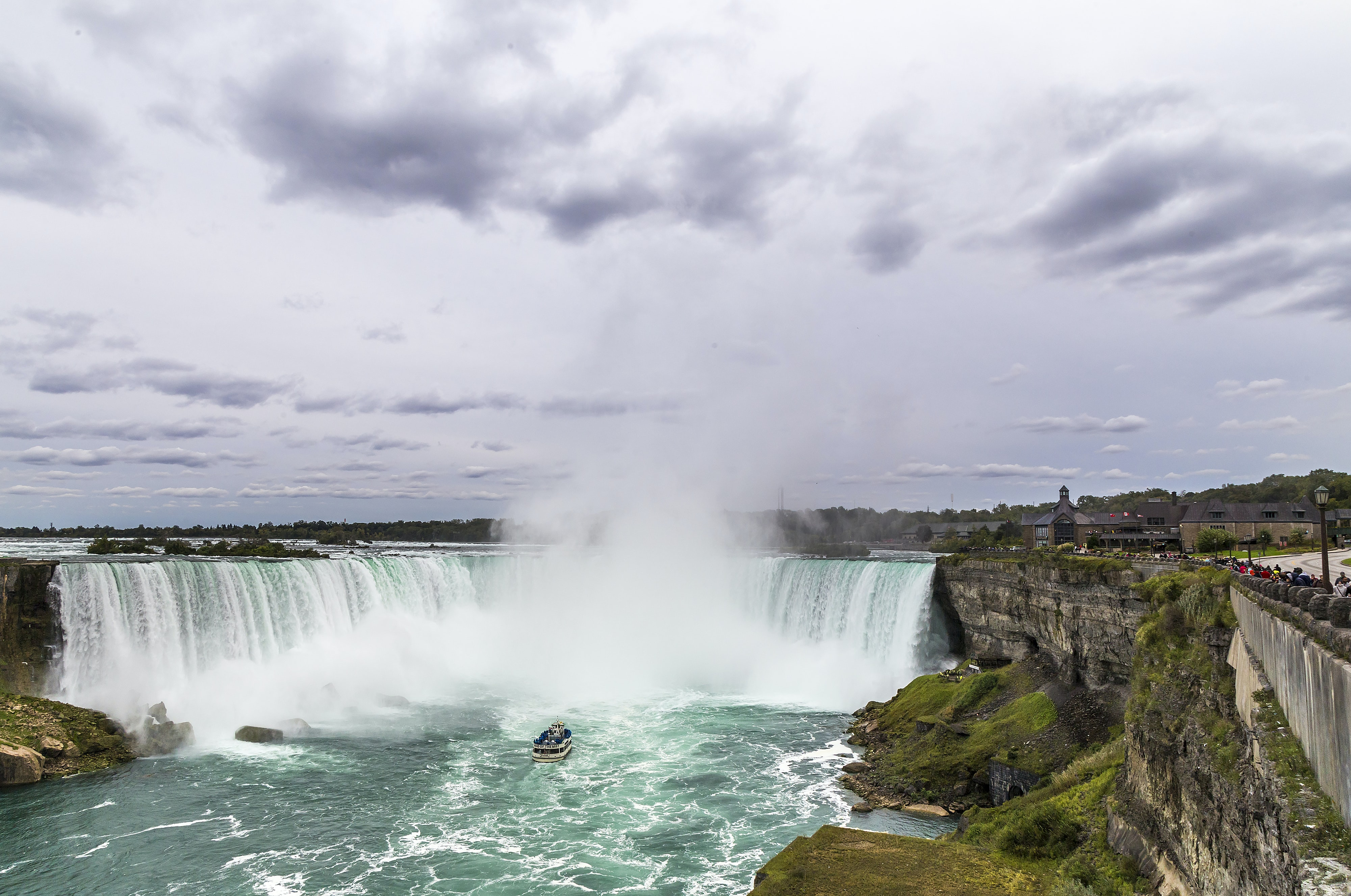 An impressive waterfall tumbling down from a rock face next to a town in Niagara Falls