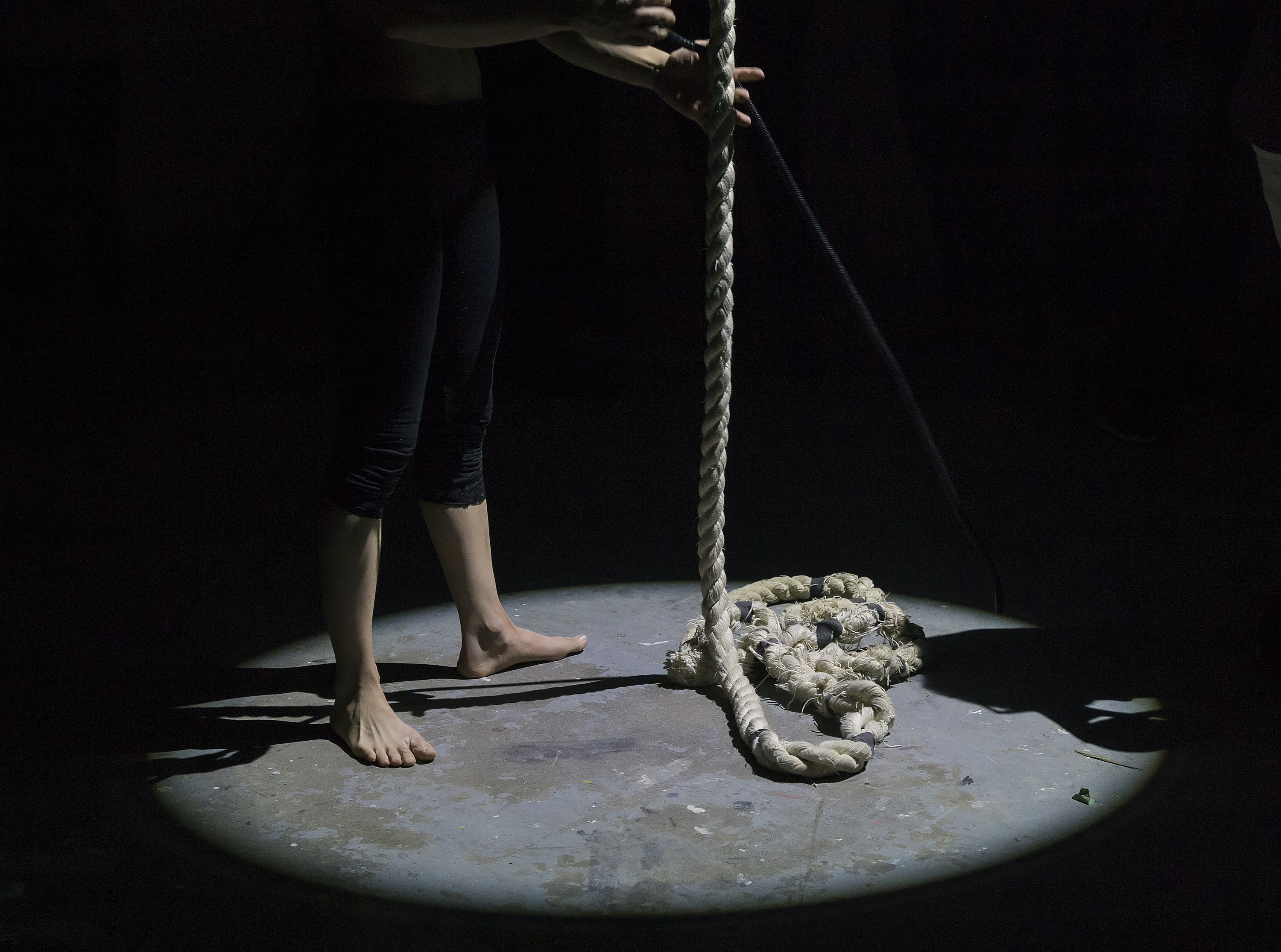 A barefoot person holding rope under a spotlight
