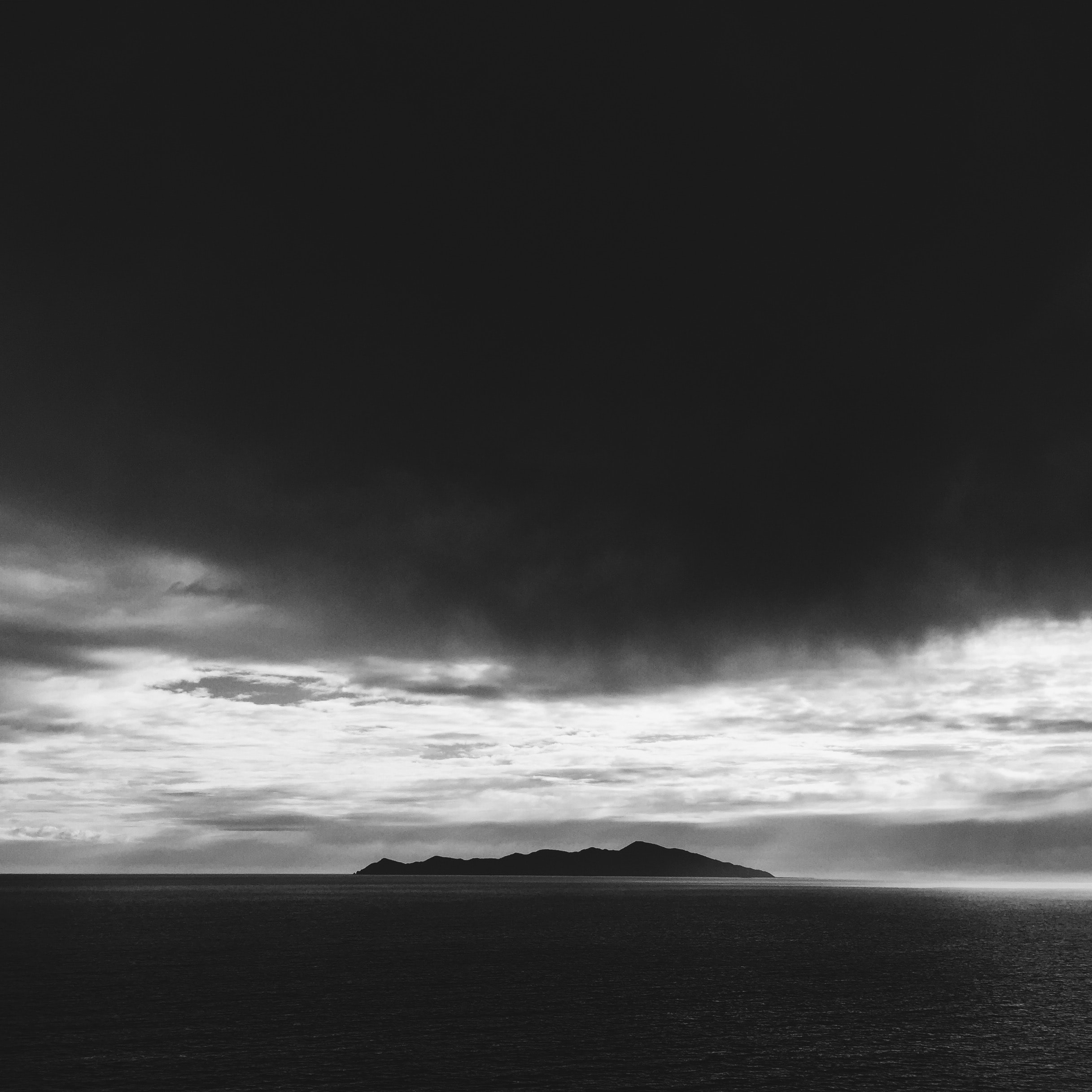 greyscale photo of an island under white clouds