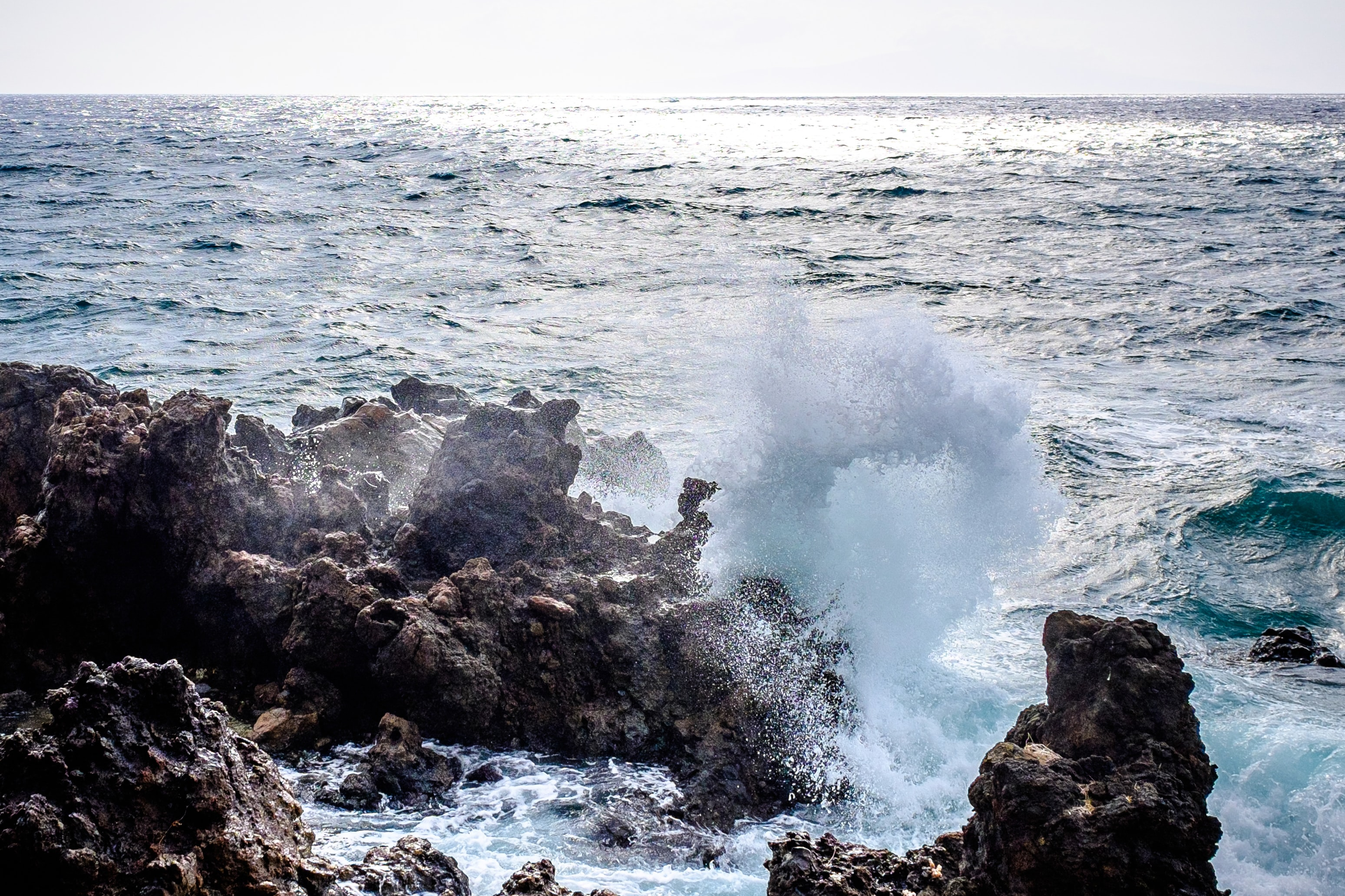 A wave breaking and splashing up onto rocks along the coast of Maui