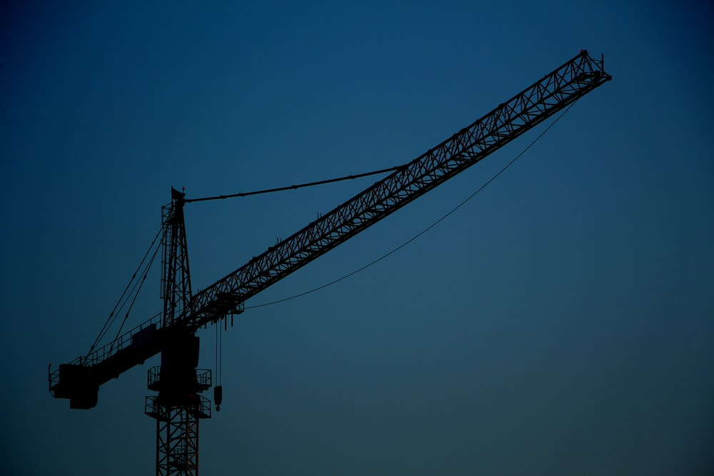 black metal crane tower under blue sky