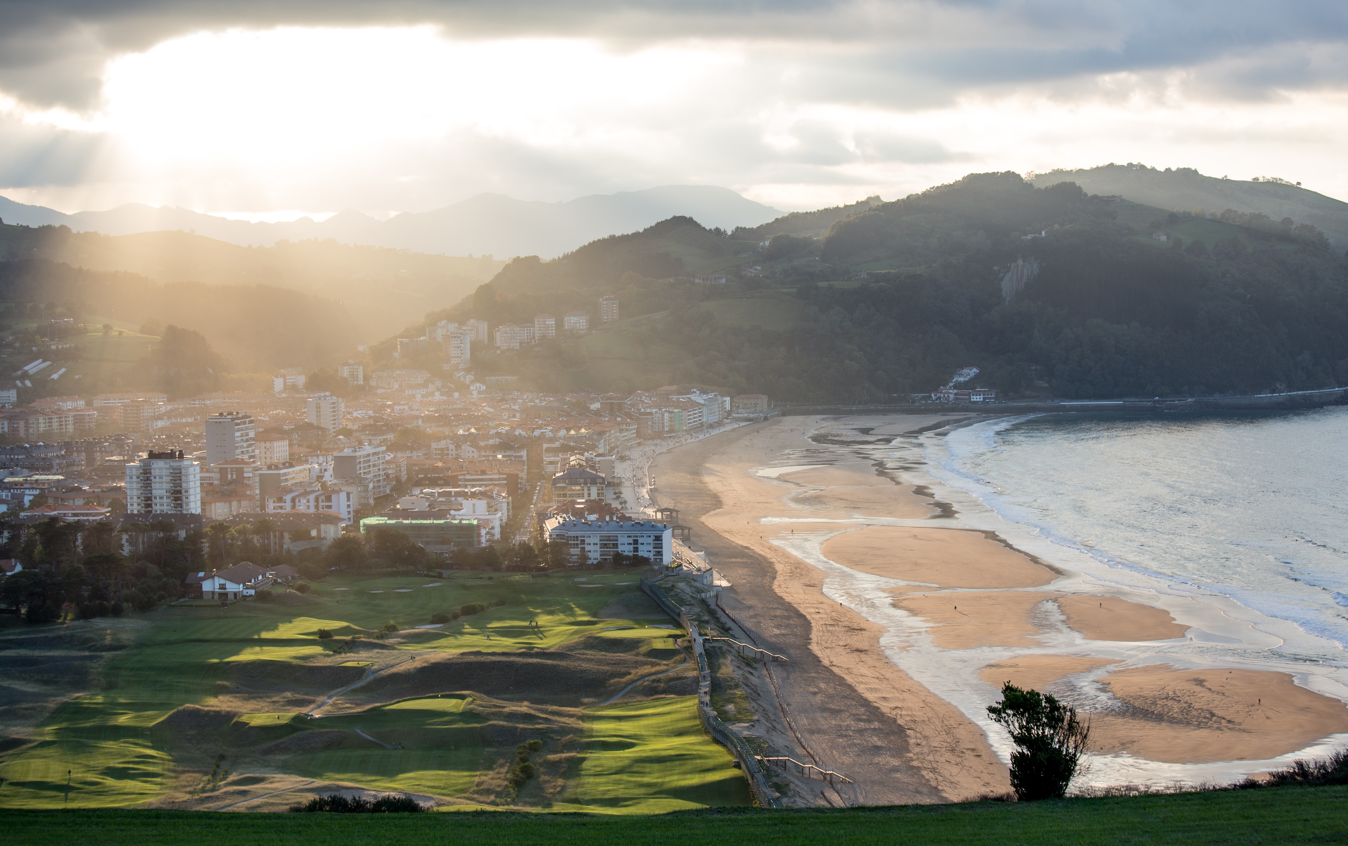 Aerial view featuring beach, settlements and surrounding landscape  of the mountains in countryside Zarautz