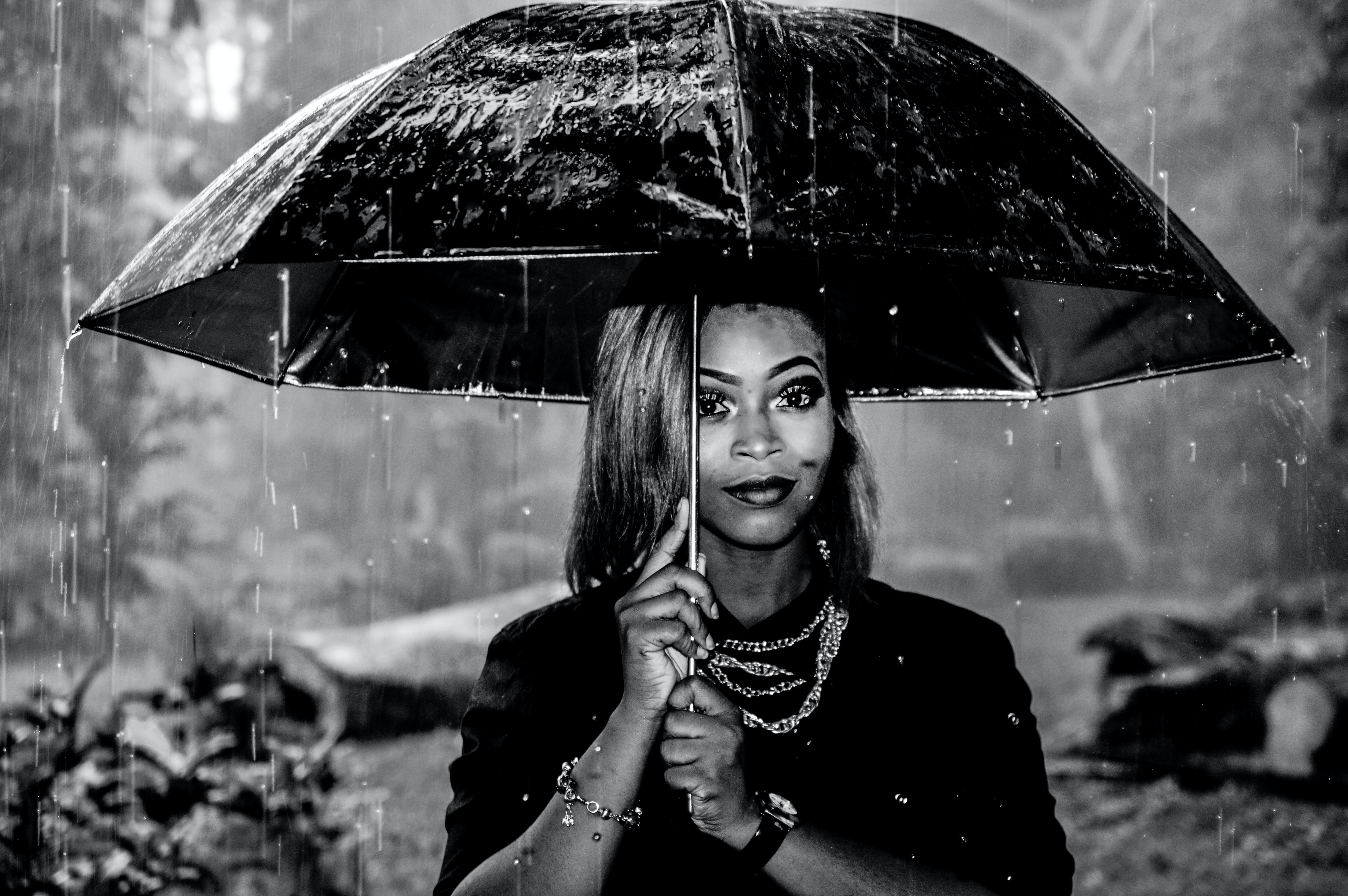 Black and white shot of fashionable woman with necklaces under umbrella in pouring rain