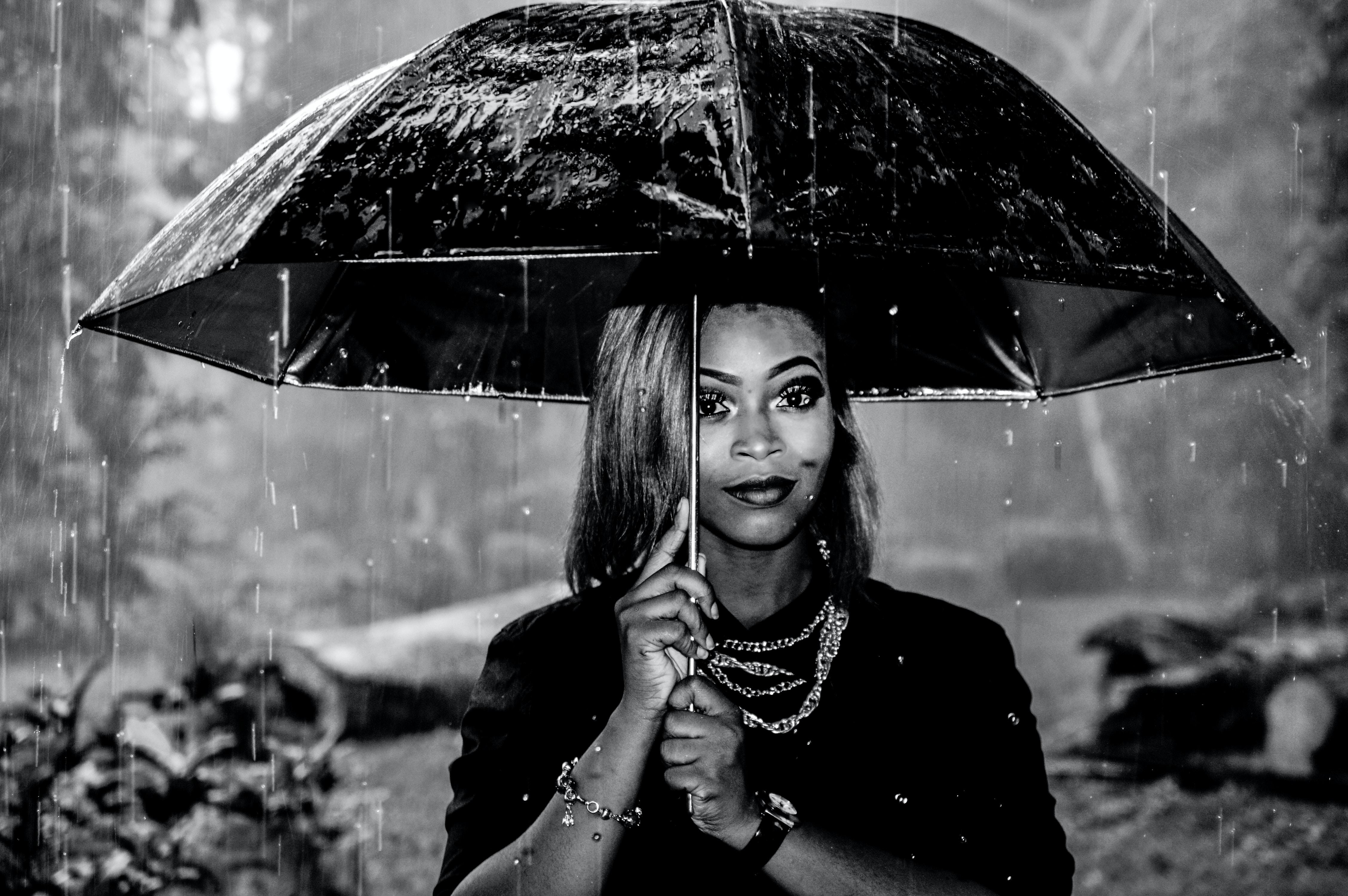 grayscale photography of woman under umbrella at rainy season