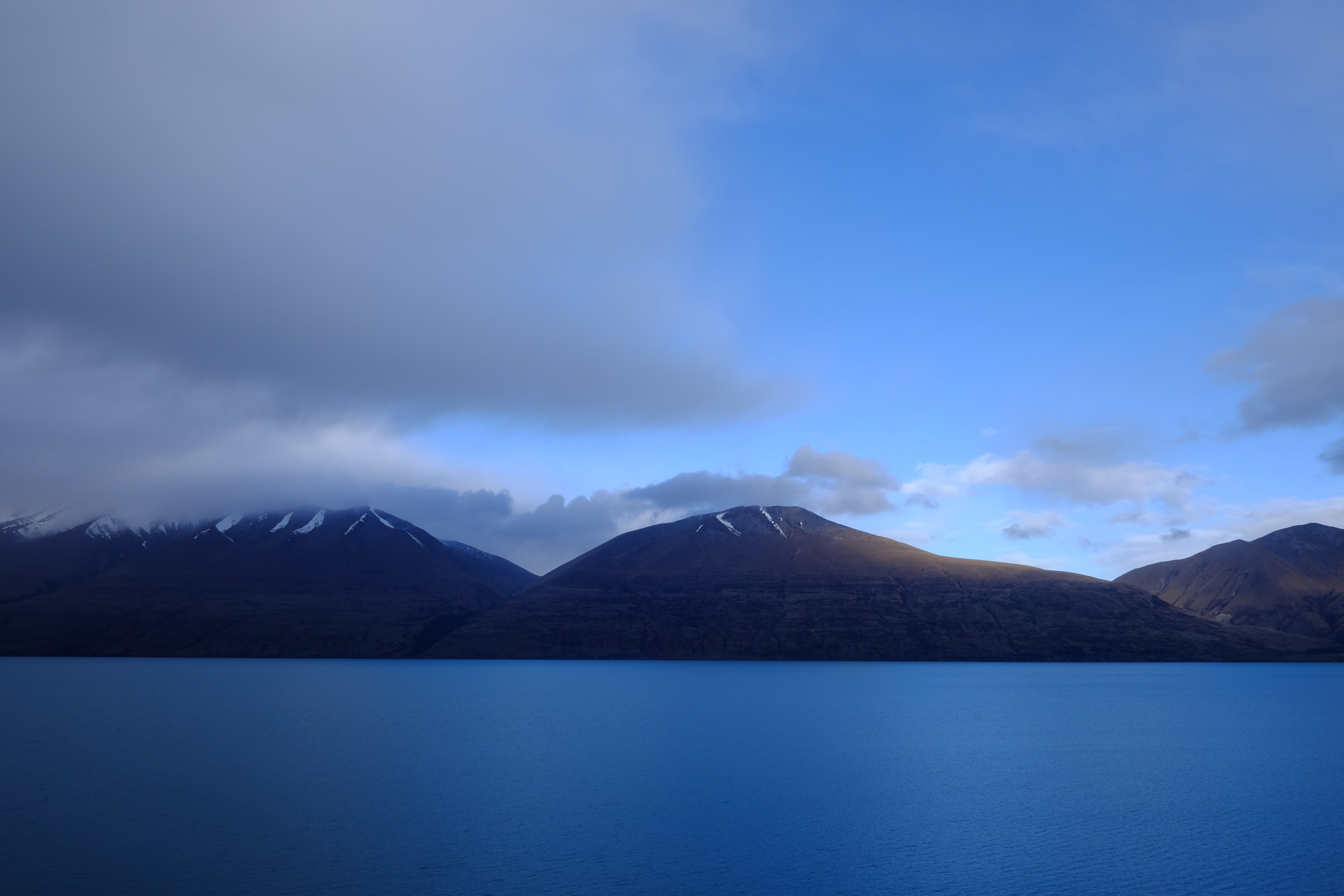 The calm surface of Lake Ohau by a mountain range under clouds