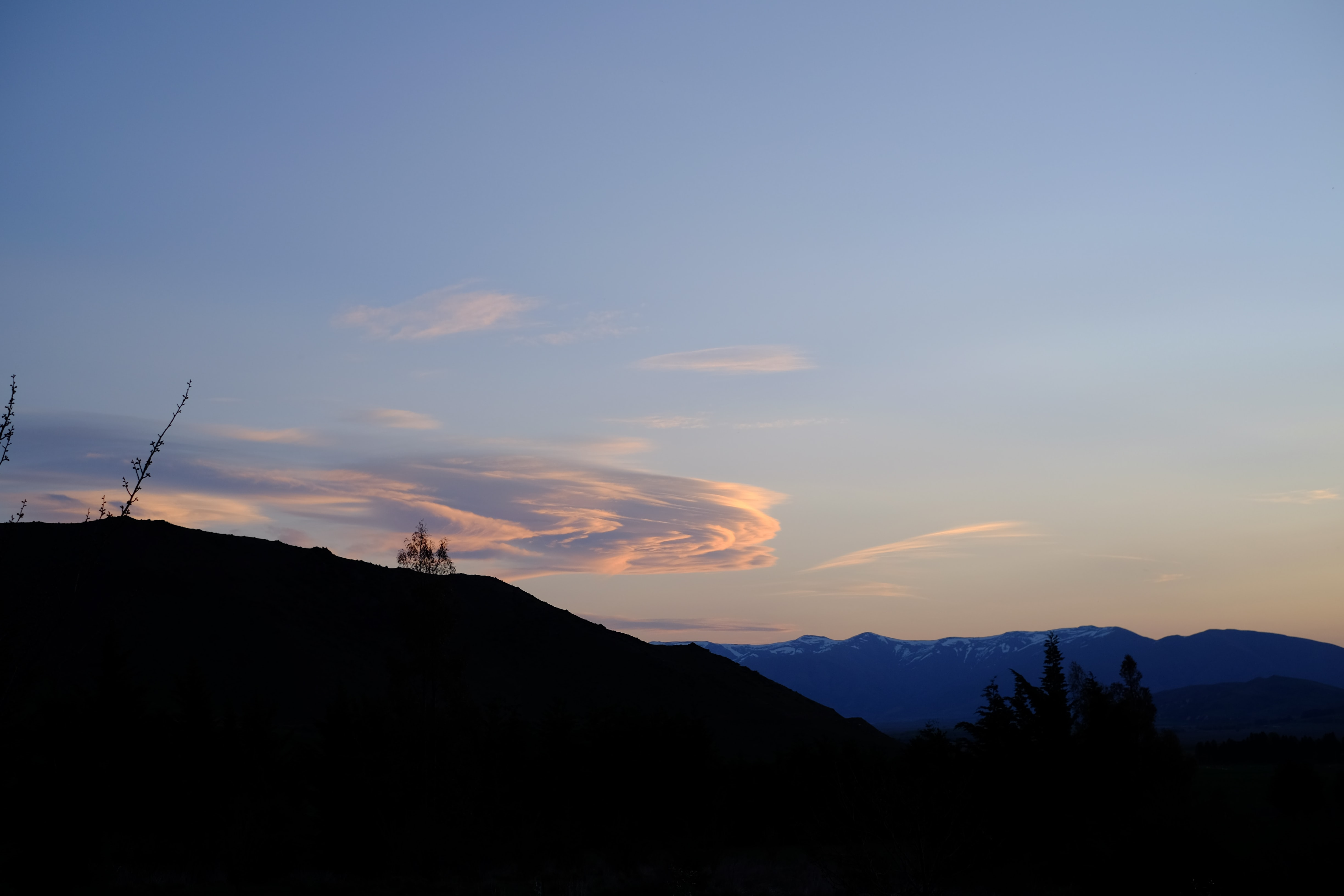 A silhouette of a mountain slope partly obscuring a tall mountain ridge on the horizon in the evening